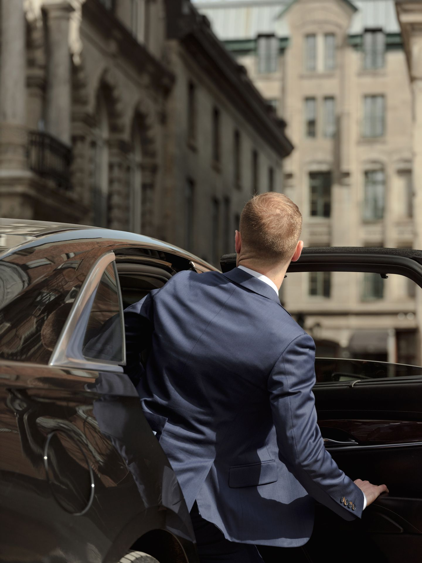 young man quickly getting in car wearing professional suit photographed by Alexi Hobbs for PSP