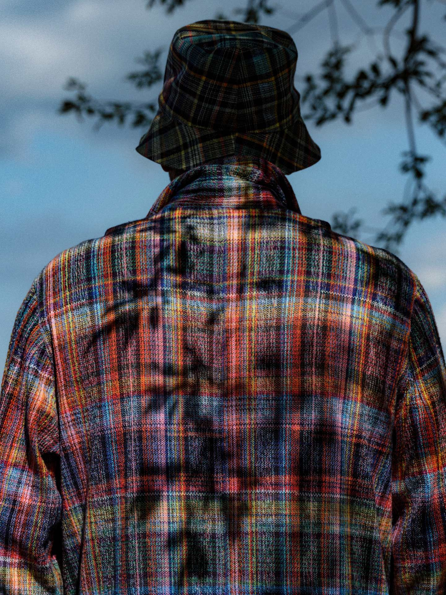 man in colourful plaid overalls back turned with shadows of tree branches on his back by Alexi Hobbs at Pinard & Filles winery for Larose Paris