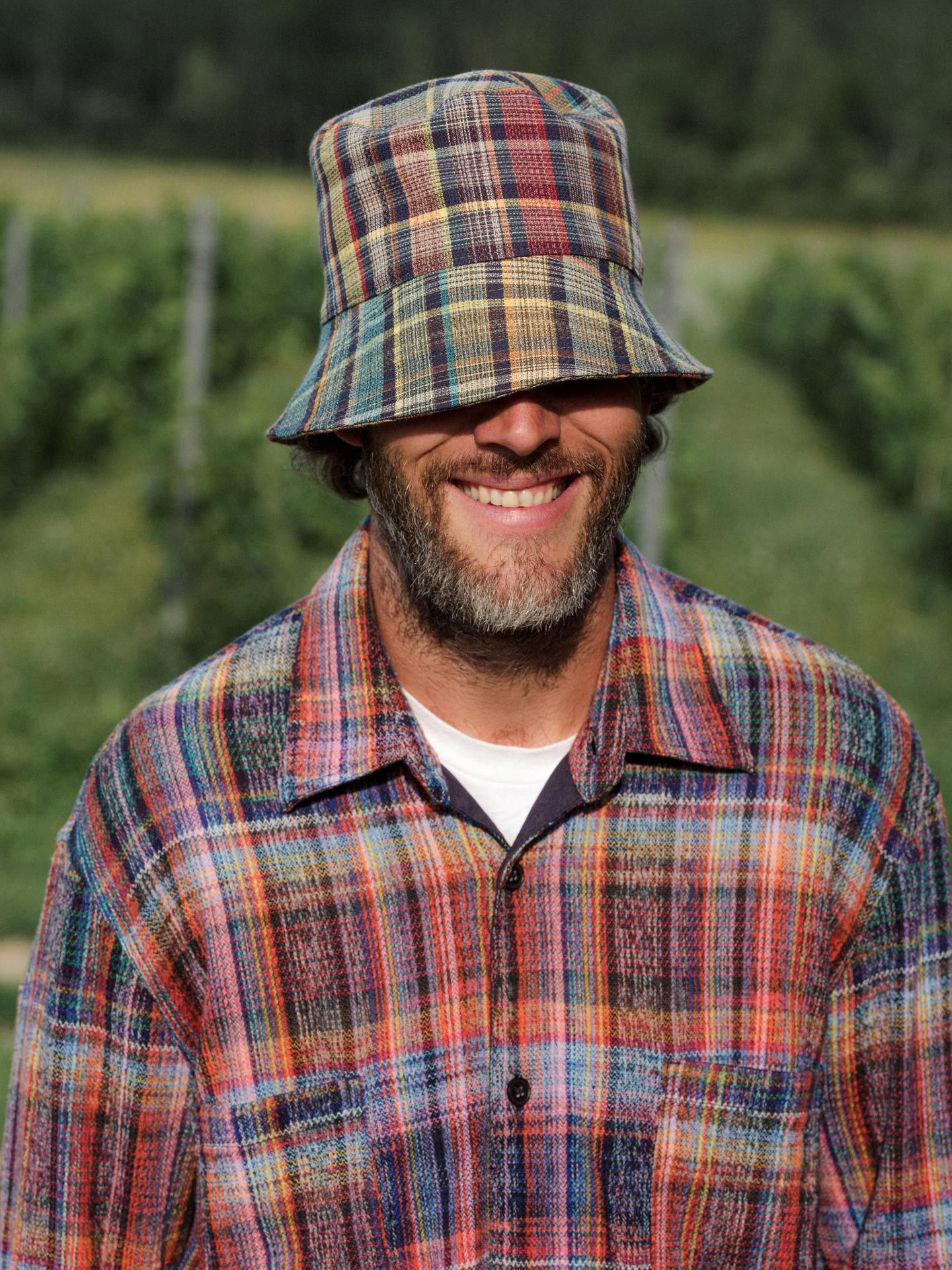 smiling winemaker in colorful plaid overalls and matching low bob hat hiding his eyes by Alexi Hobbs at Pinard & Filles for Larose Paris
