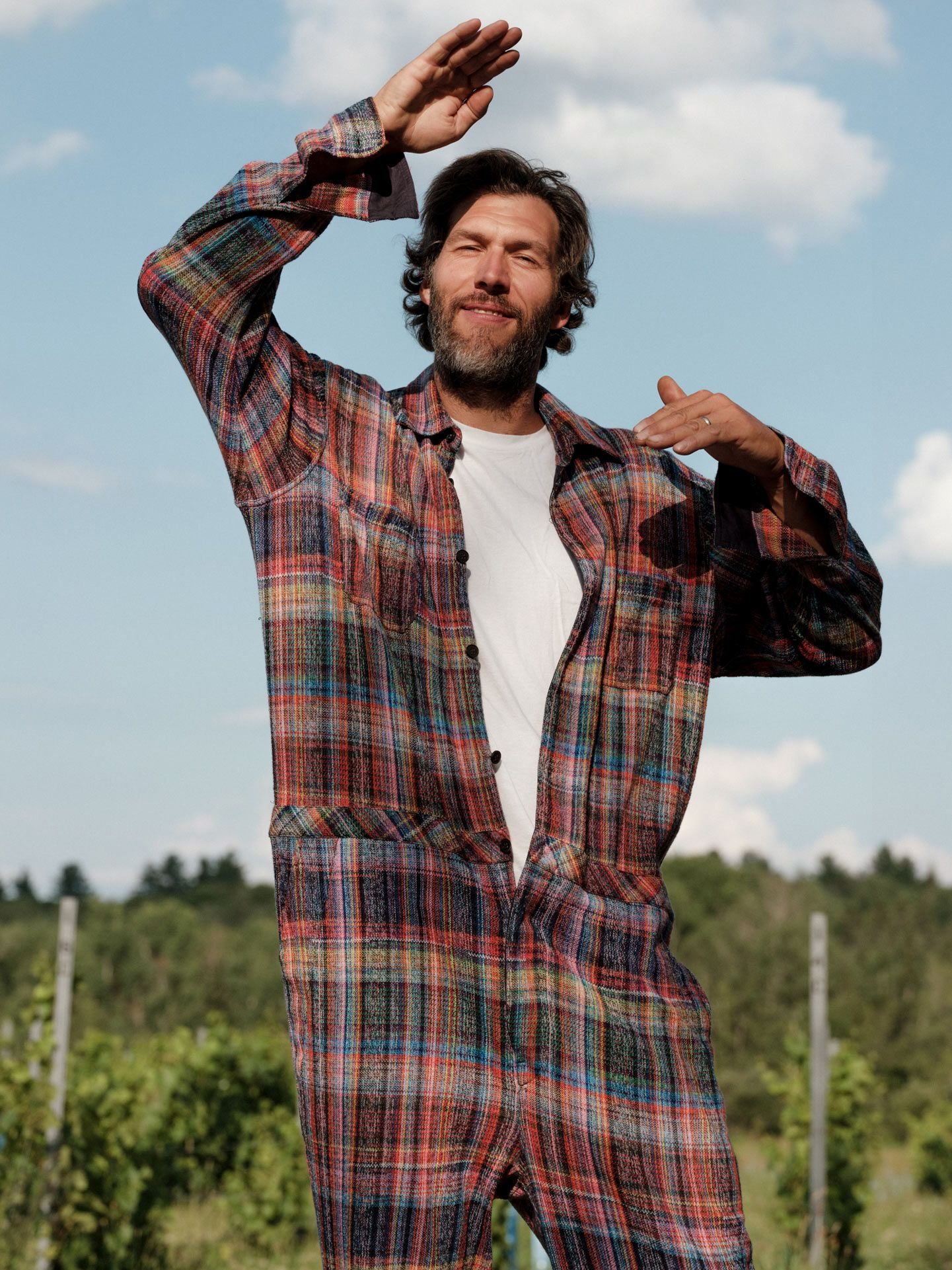 man in field wearing colorful plaid overalls face in the sun raising his hand to shade his eyes by Alexi Hobbs at Pinard & Filles winery for Larose Paris