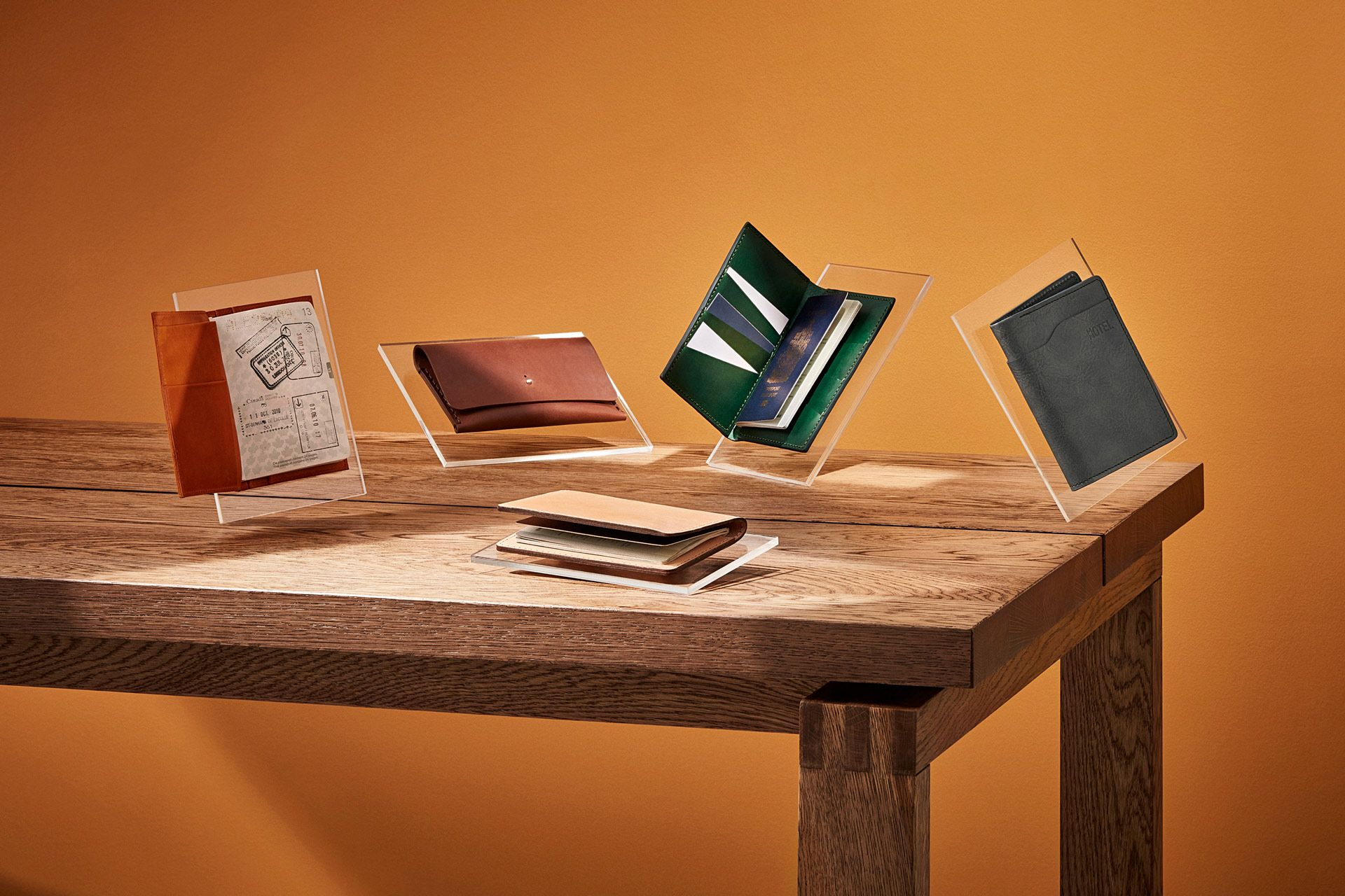 wood tables presenting different types of wallets floating in the air by Mathieu Levesque for enRoute