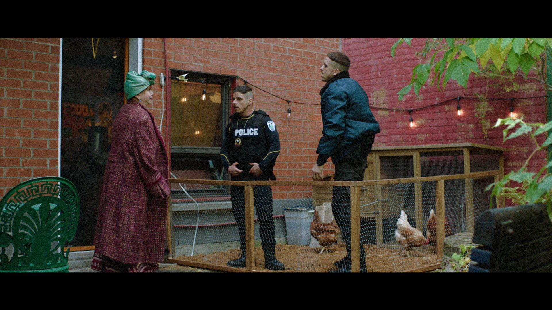 actors Hugolin Chevrette-Landesque and Emile Schneider posing as cops in a chicken coop for TV series La Loi C'est La Loi filmed by Les Gamins for TV5 Unis
