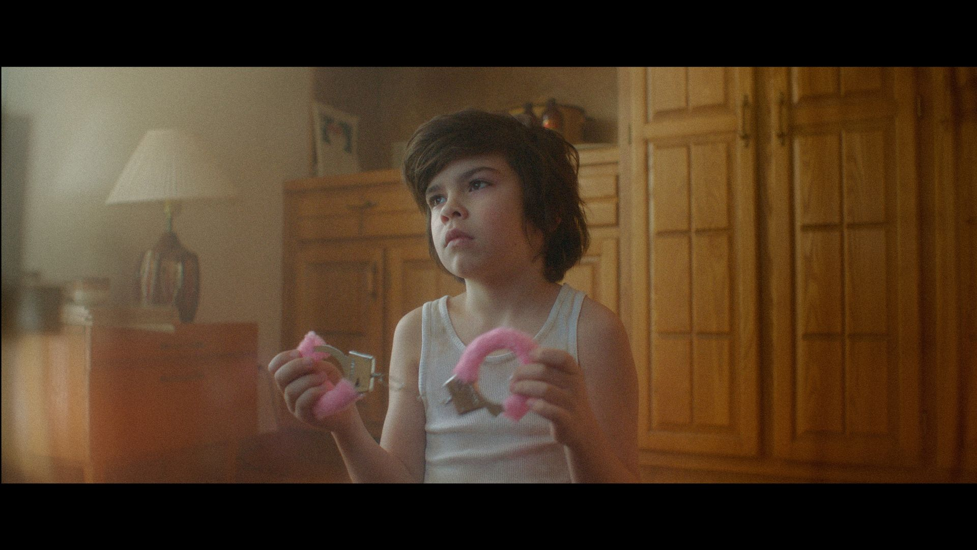 kid looking at TV holding fuzzy pink handcuffs in TV series La Loi C'est La Loi filmed by Les Gamins
