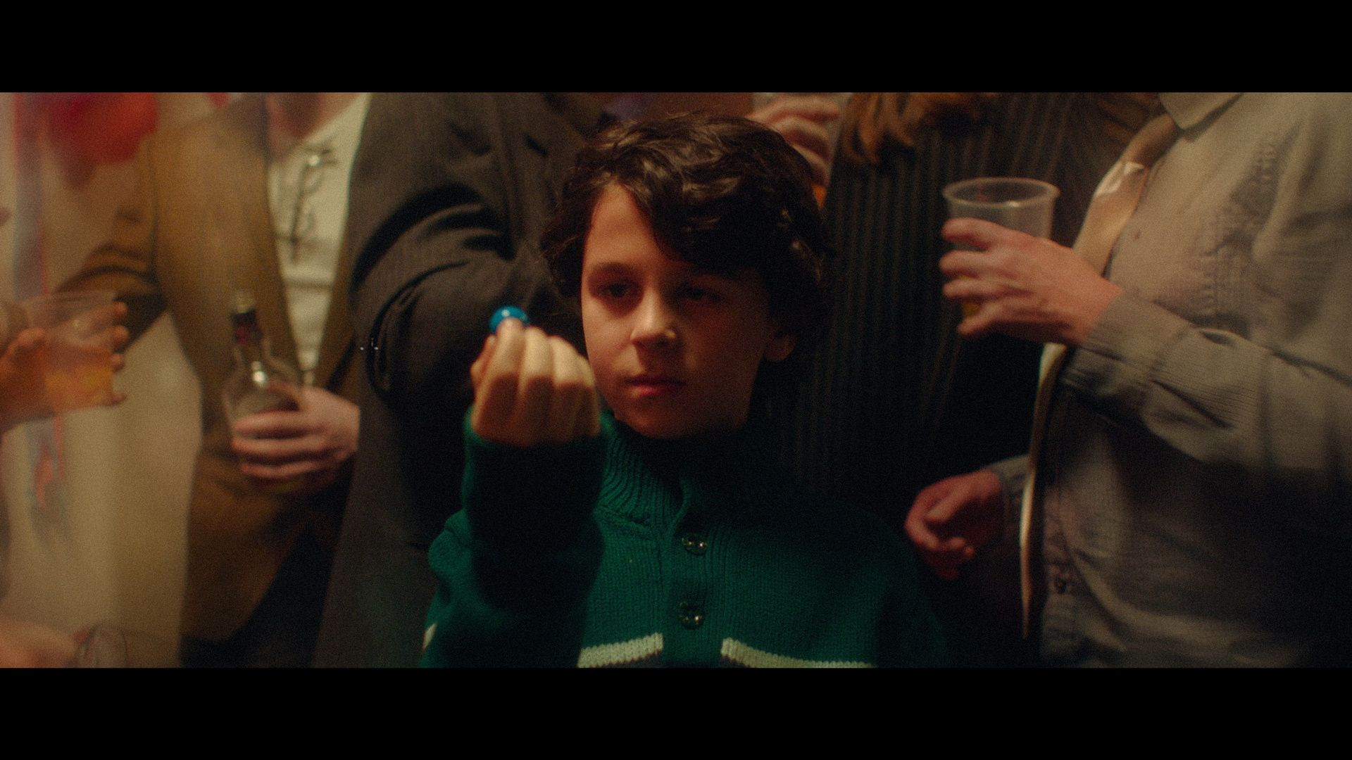 young boy holding bubblegum ball in the middle of raging party for TV series La Loi C'est La Loi filmed by Les Gamins for TV5 Unis