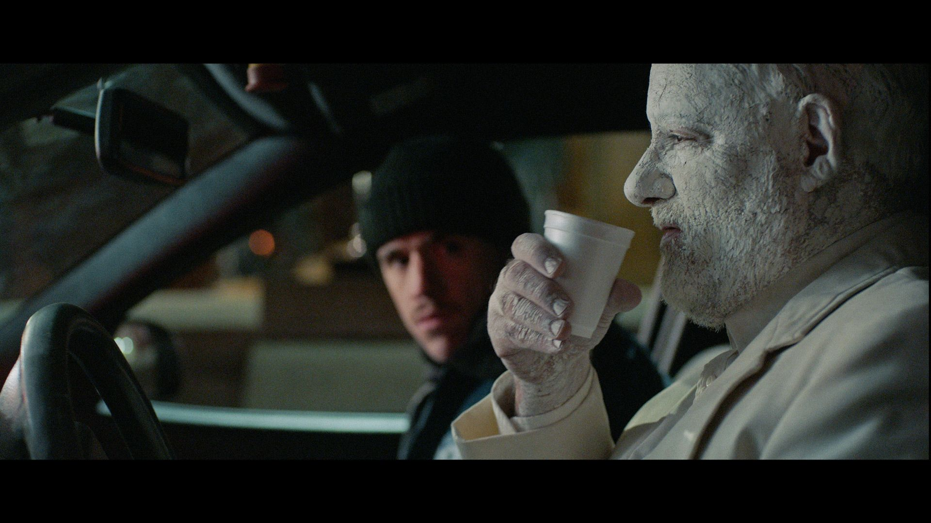 actor Emile Schneider posing as cop in a car sitting next to man completely painted white drinking a cup of water for TV series La Loi C'est La Loi filmed by Les Gamins for TV5 Unis
