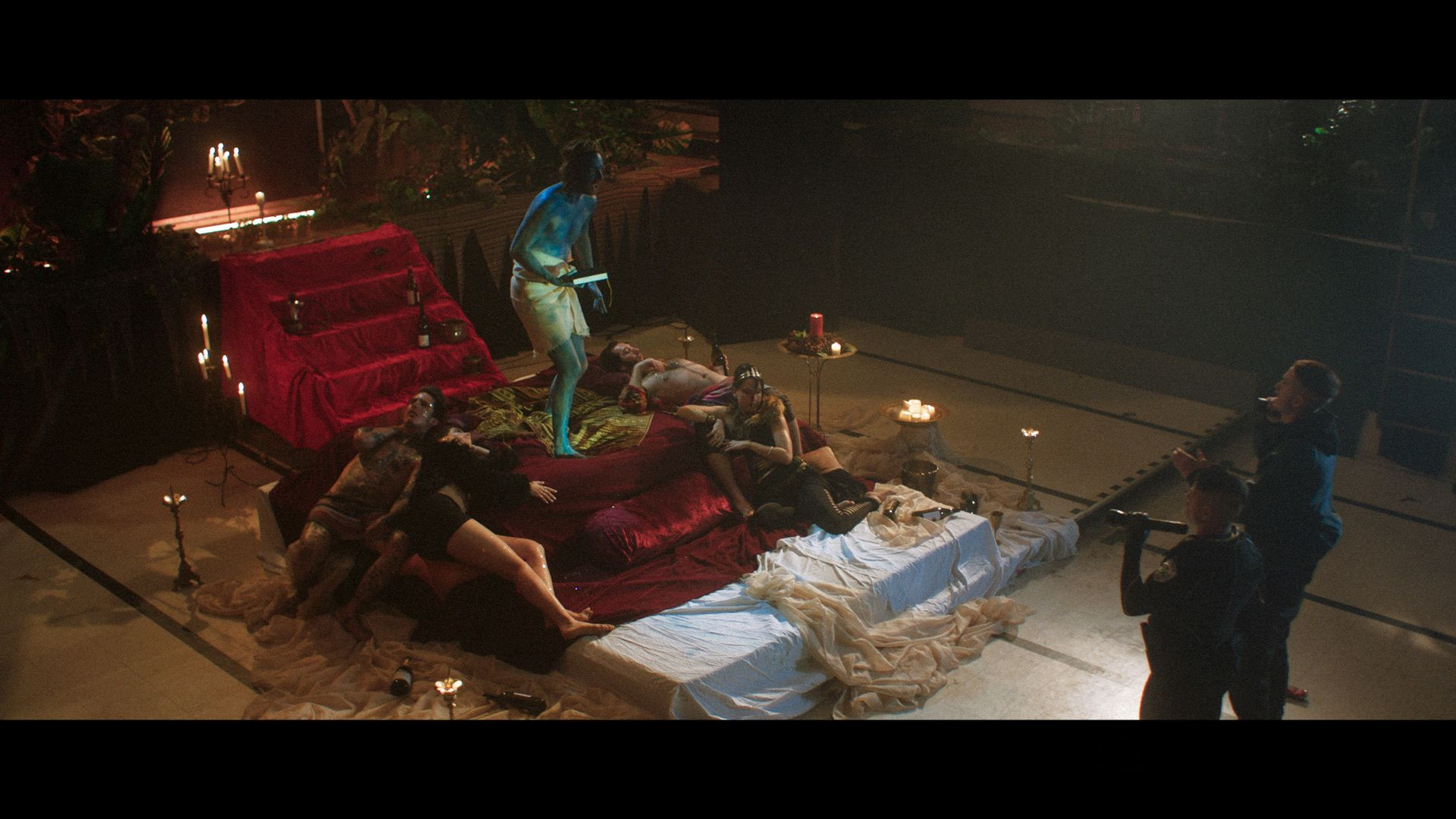 actor completely painted in blue from head to toe playing a guru standing on stage-bed surrounded by people laying blissfully at his feet while guru screams at police officers played by Hugolin Chevrette-Landesque and Emile Schneider for TV series La Loi C'est La Loi filmed by Les Gamins for TV5 Unis