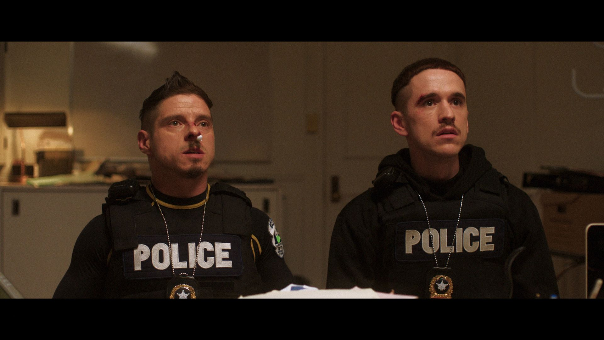 actors Hugolin Chevrette-Landesque and Emile Schneider posing as cops looking beaten up with noses bleeding sitting in their chief's office for TV series La Loi C'est La Loi filmed by Les Gamins for TV5 Unis