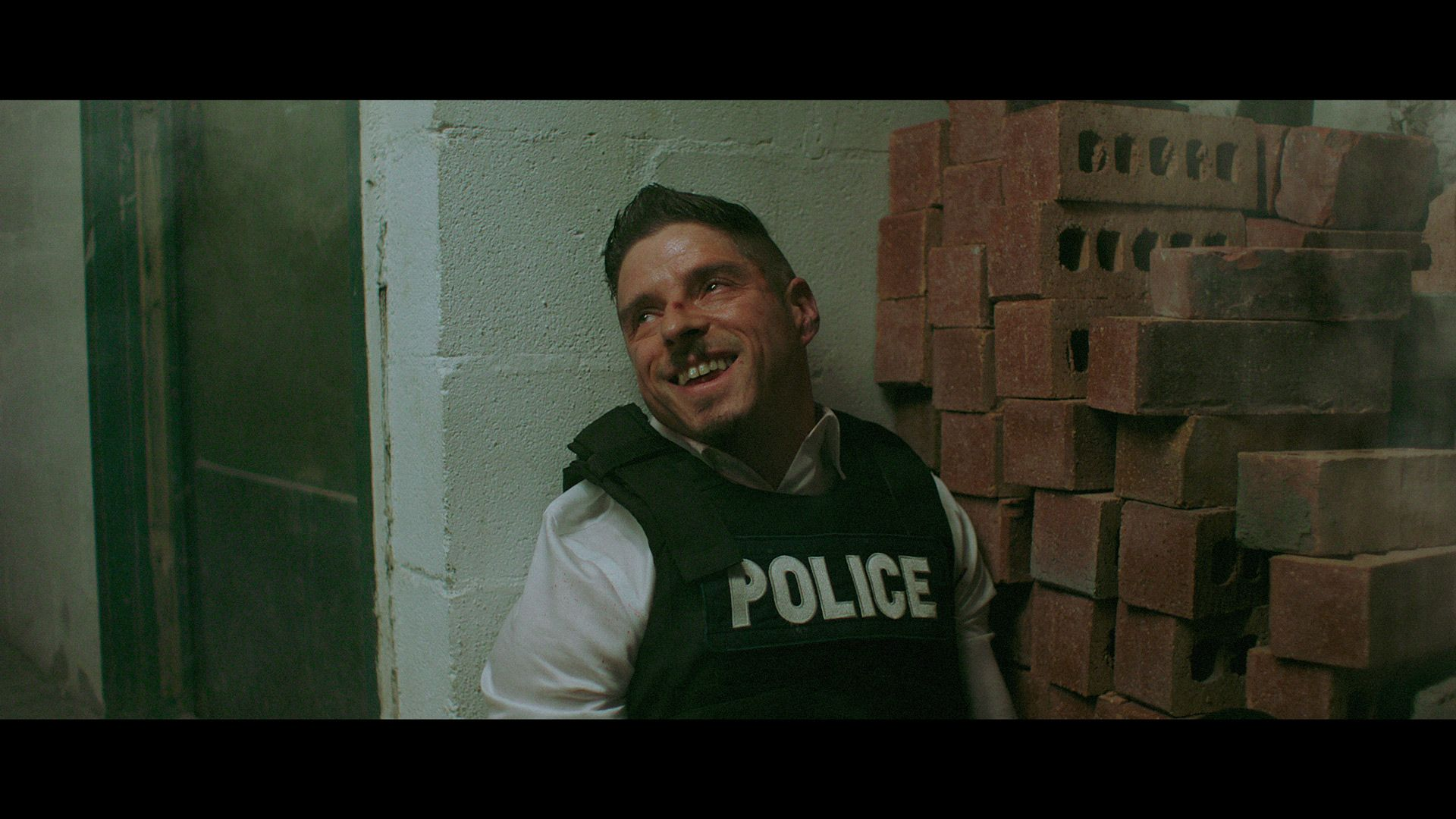 actors Hugolin Chevrette-Landesque posing as cop brassed against a wall looking delirious for TV series La Loi C'est La Loi filmed by Les Gamins for TV5 Unis