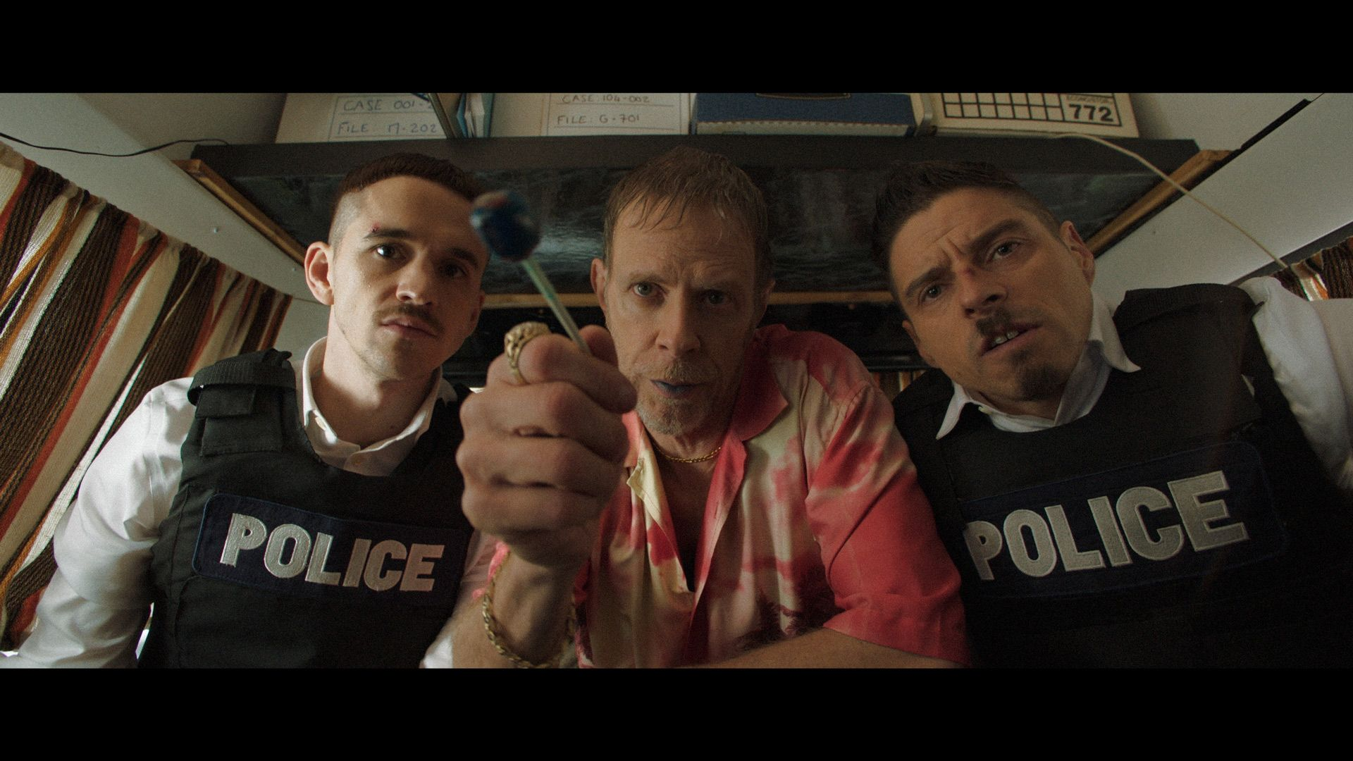 actors Hugolin Chevrette-Landesque and Emile Schneider posing as cops on each side of a man in tie-dye shirt holding a blue lollipop with blue lips looking at camera for TV series La Loi C'est La Loi filmed by Les Gamins for TV5 Unis
