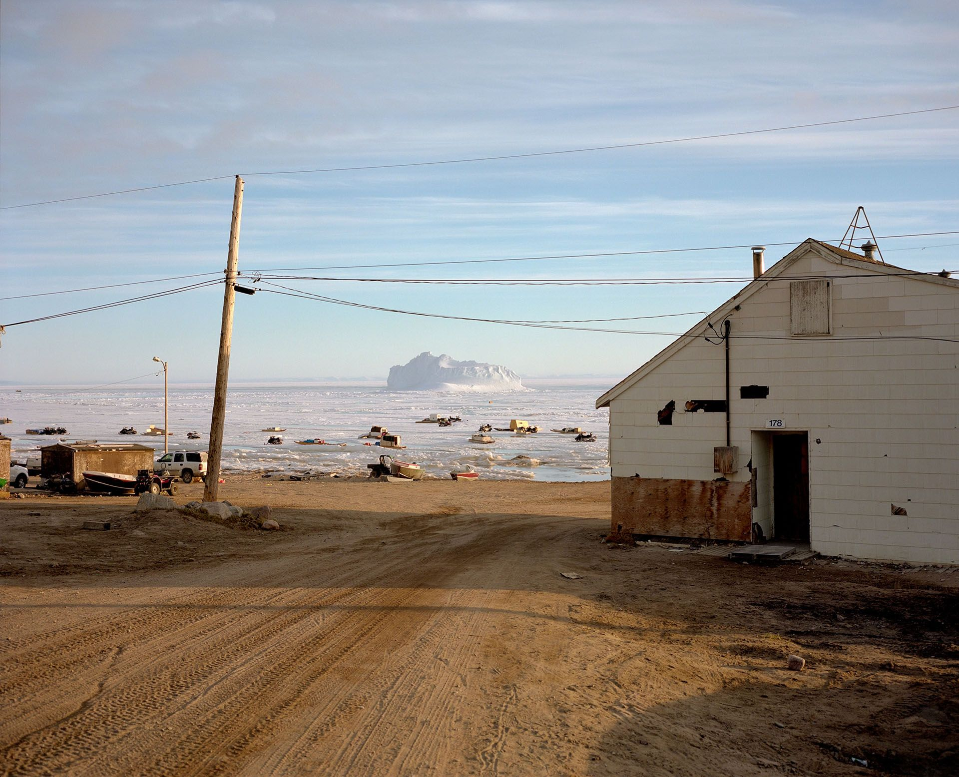 landscape dirt road with little house on the side and ice plates with boats of inuits in the background photographed by Guillaume Simoneau in Pond Inlet for Telegraph magazine