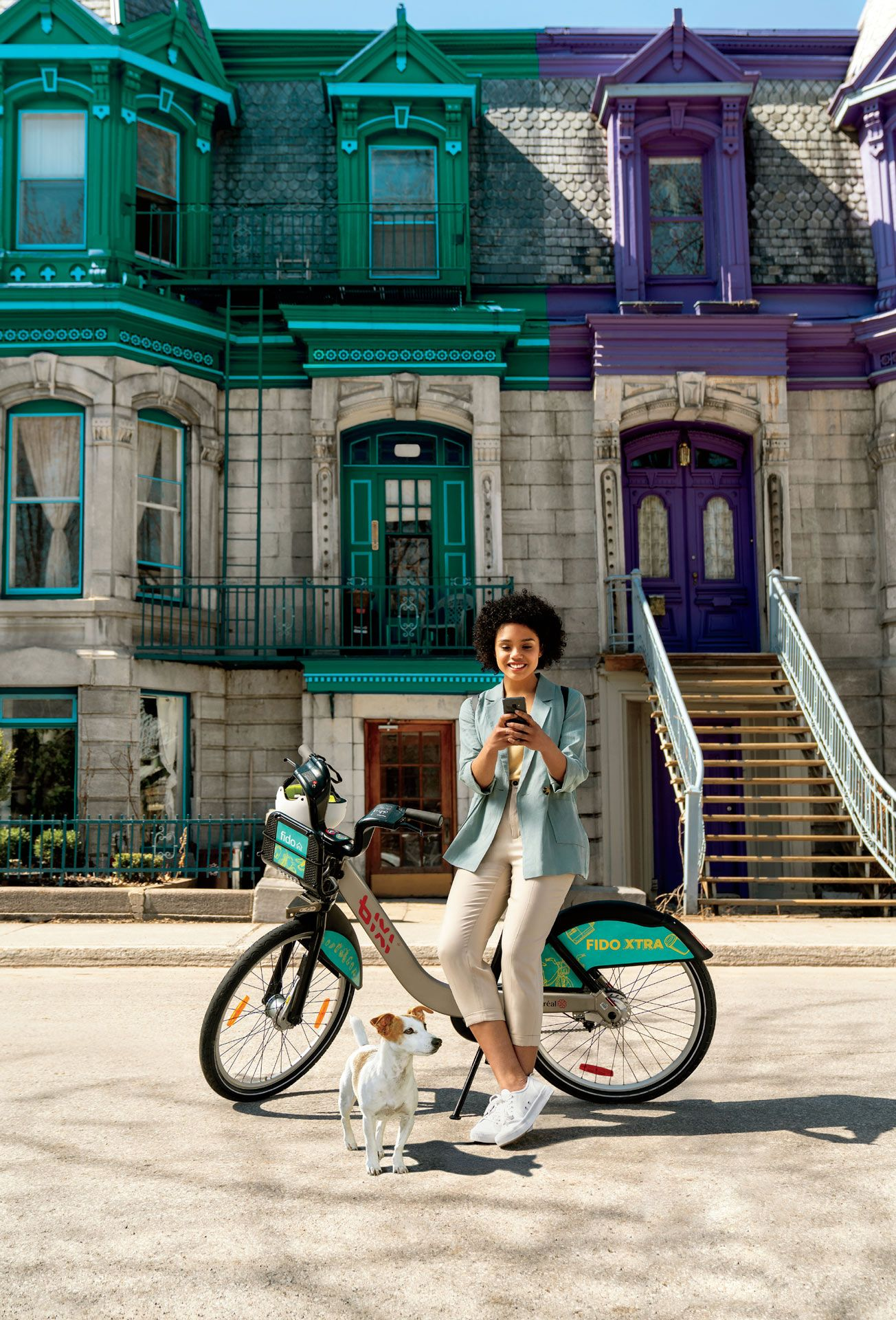 black young woman sitting on Bixi bike smiling at her phone a dog at her feet by Bruno Florin for Fido Bixi with Taxi Agency