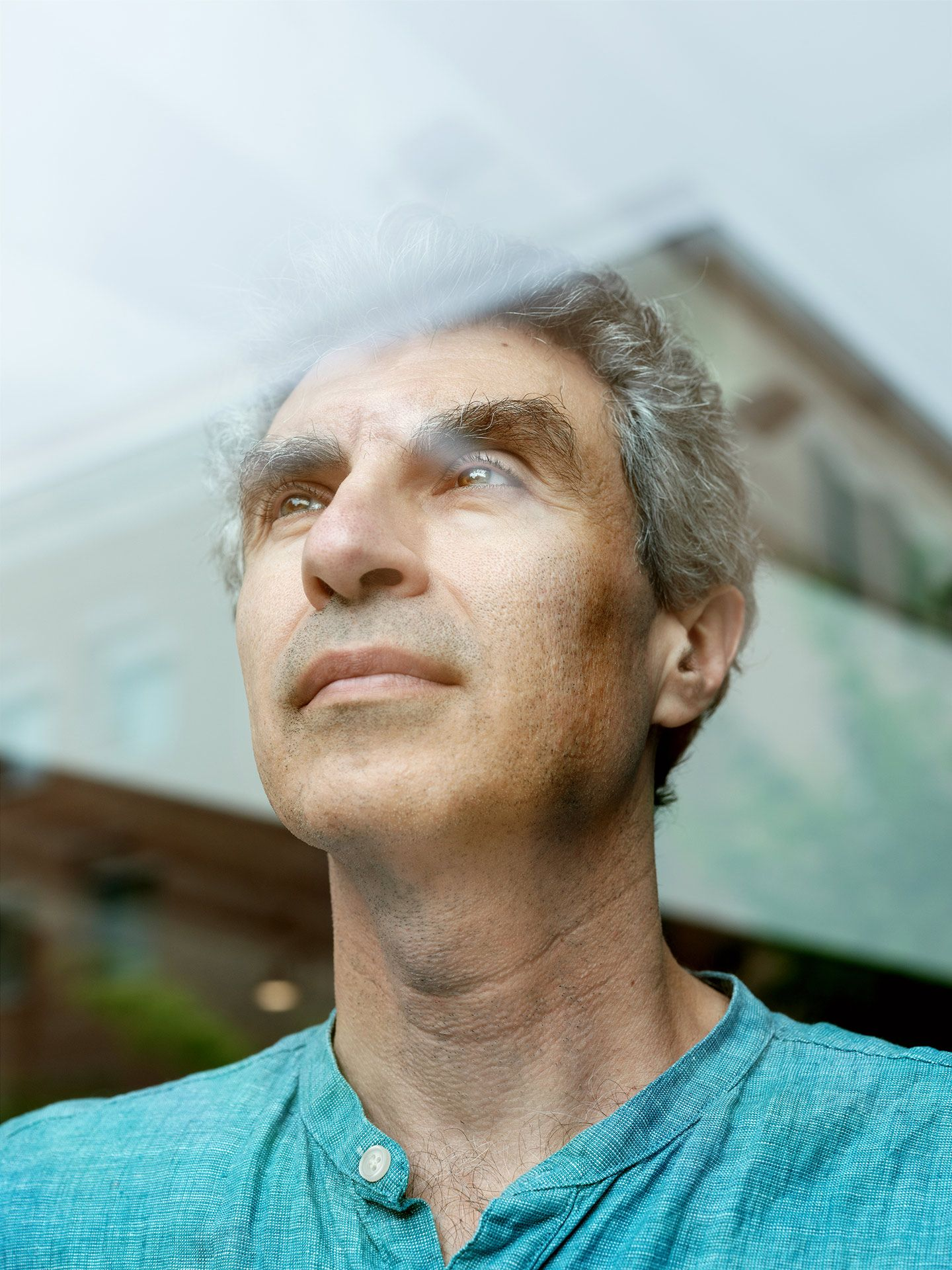 man with grey hair looking through a window by Guillaume Simoneau for Element AI with Fortune Magazine