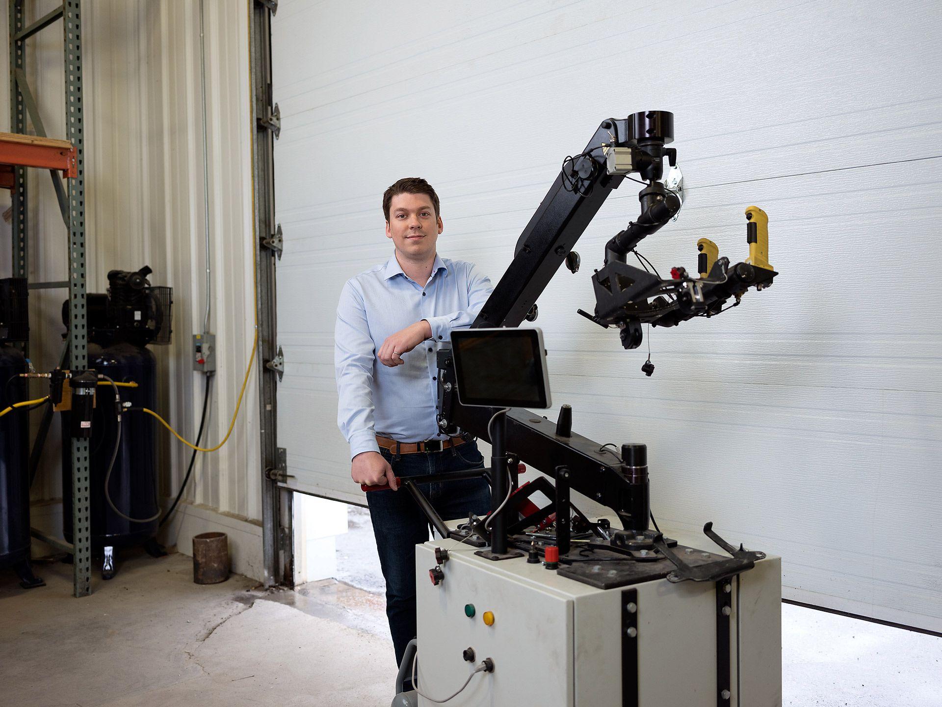 Machine laser à bras noir avec un créateur debout à côté d'elle dans un garage.