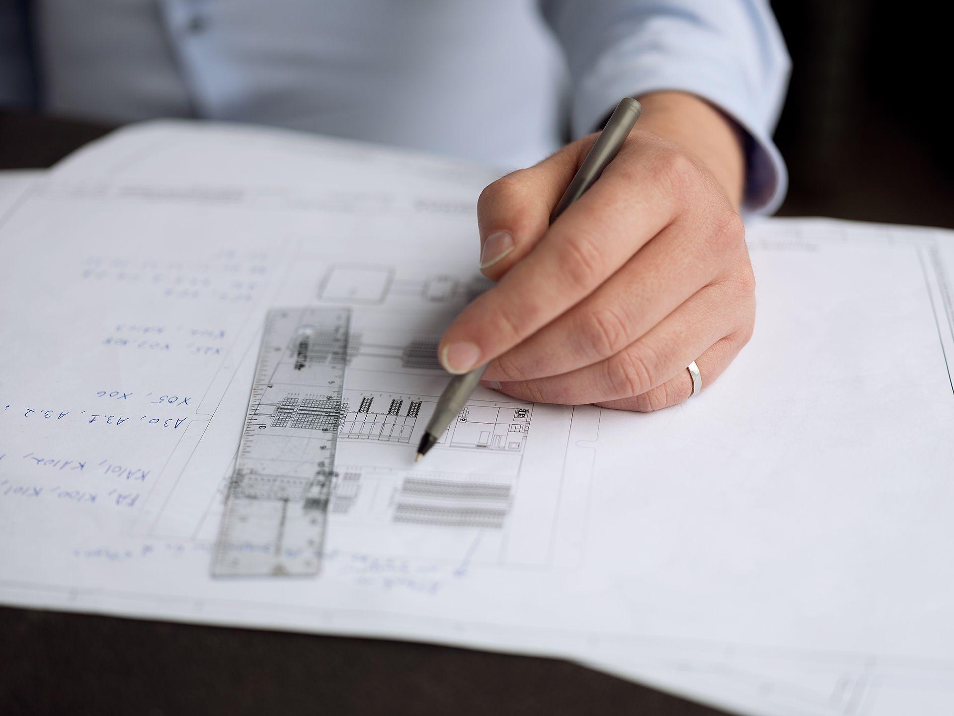 Gros plan d'une main sur un plan de machine laser, prenant des notes dessus.