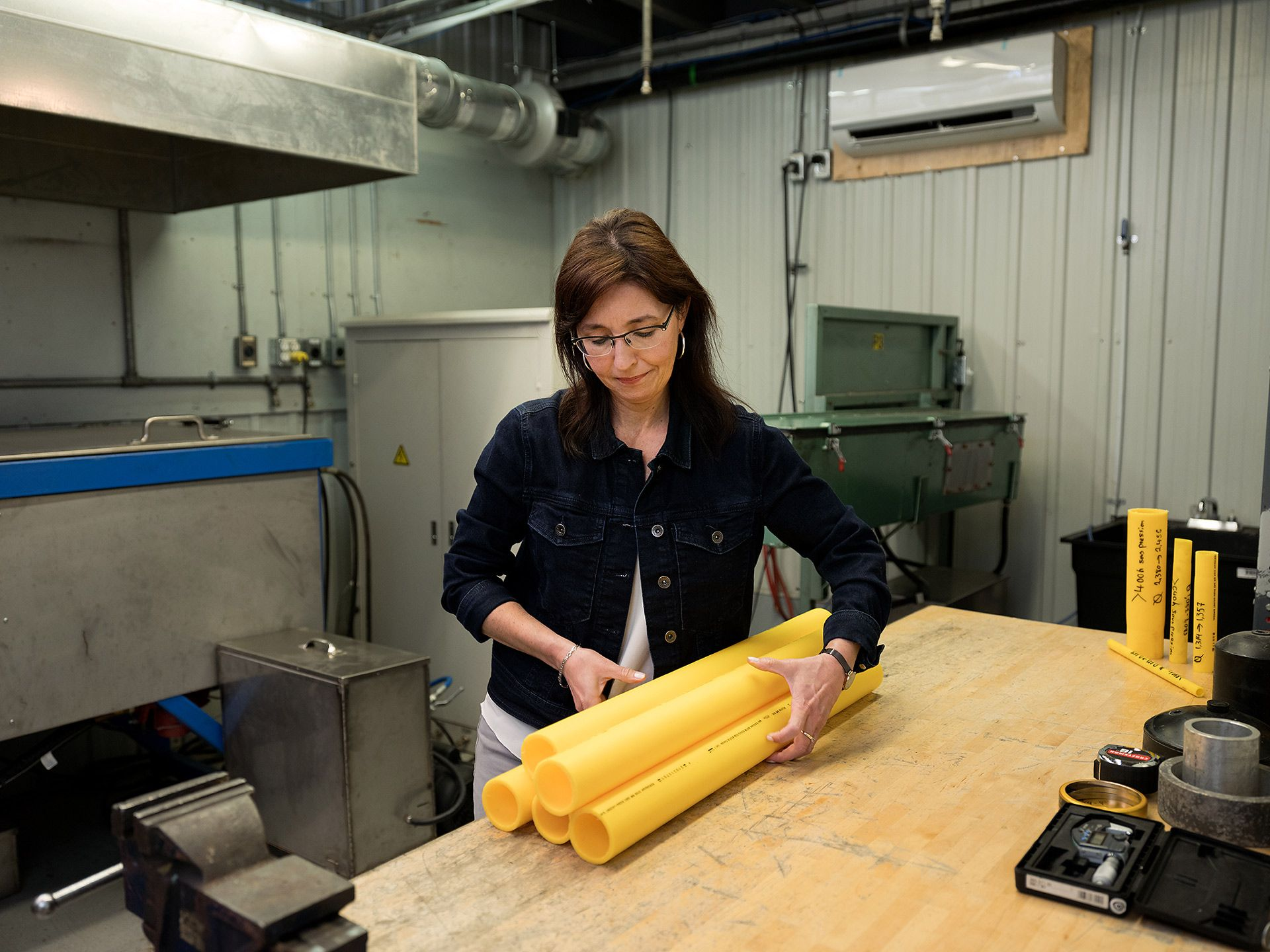 Woman in a factory grabbing 5 yellow pipes on a table.