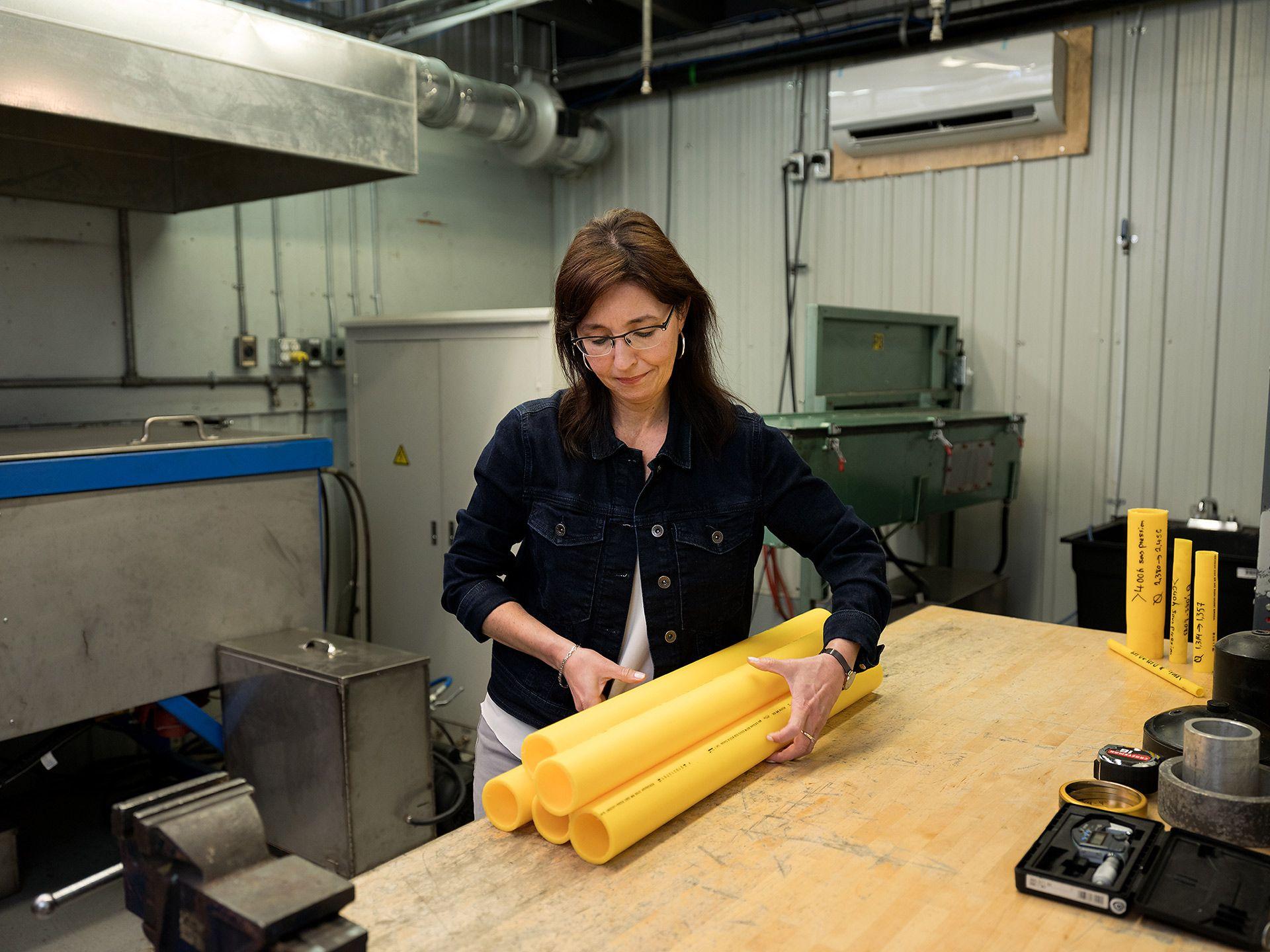 Femme dans une usine saisissant 5 tuyaux jaunes sur une table.