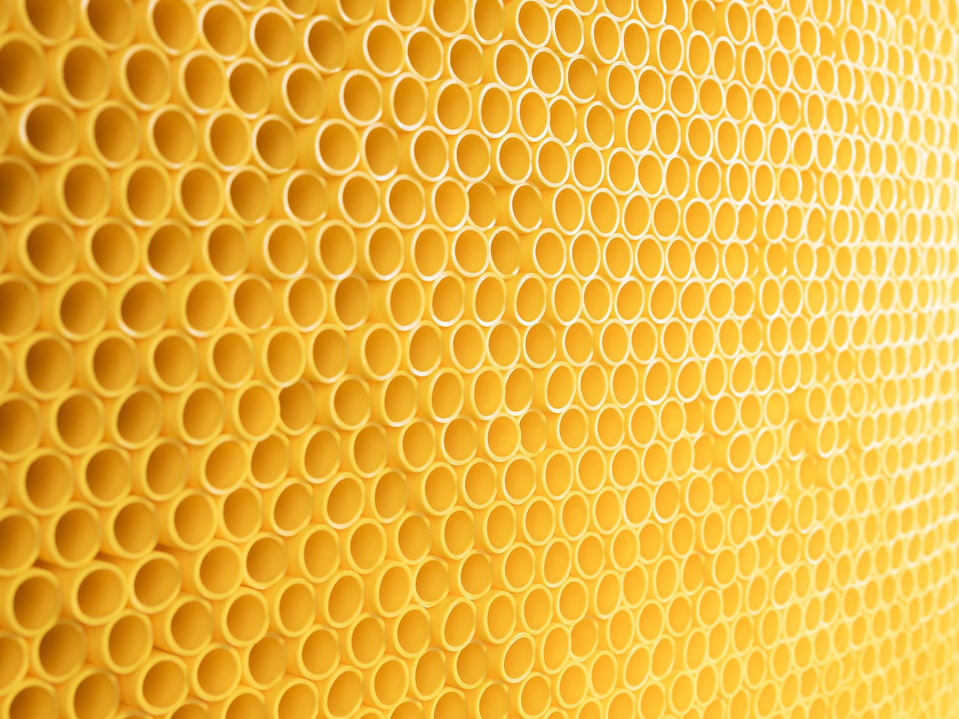 Un mur de tuyaux jaunes empilés les uns sur les autres.