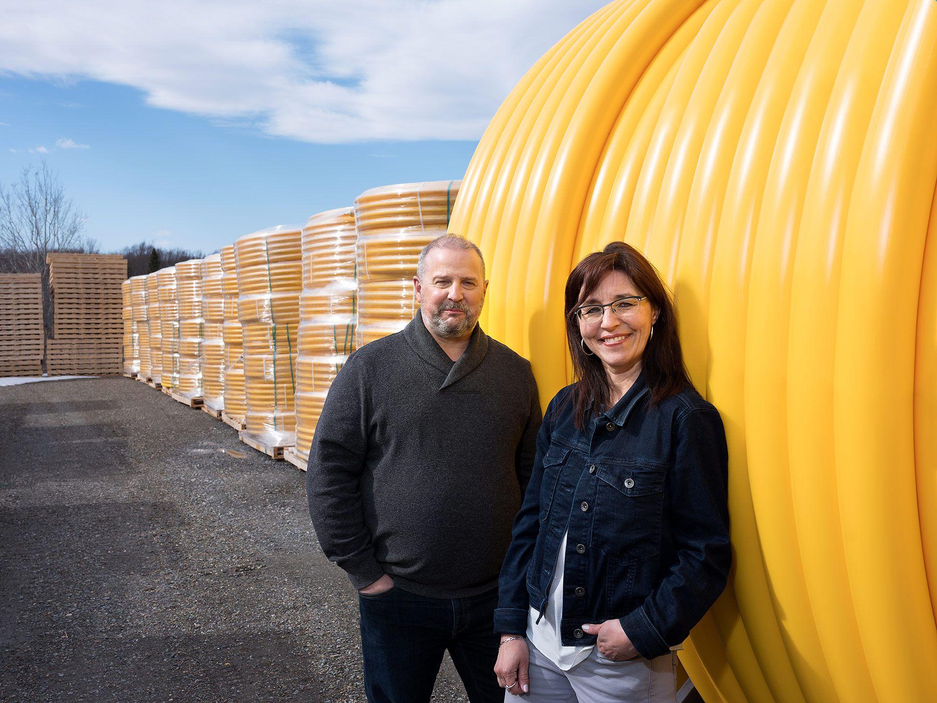 Deux fondateurs de l'entreprise de tuyaux Versaprofiles posant contre leur matériel à l'extérieur.