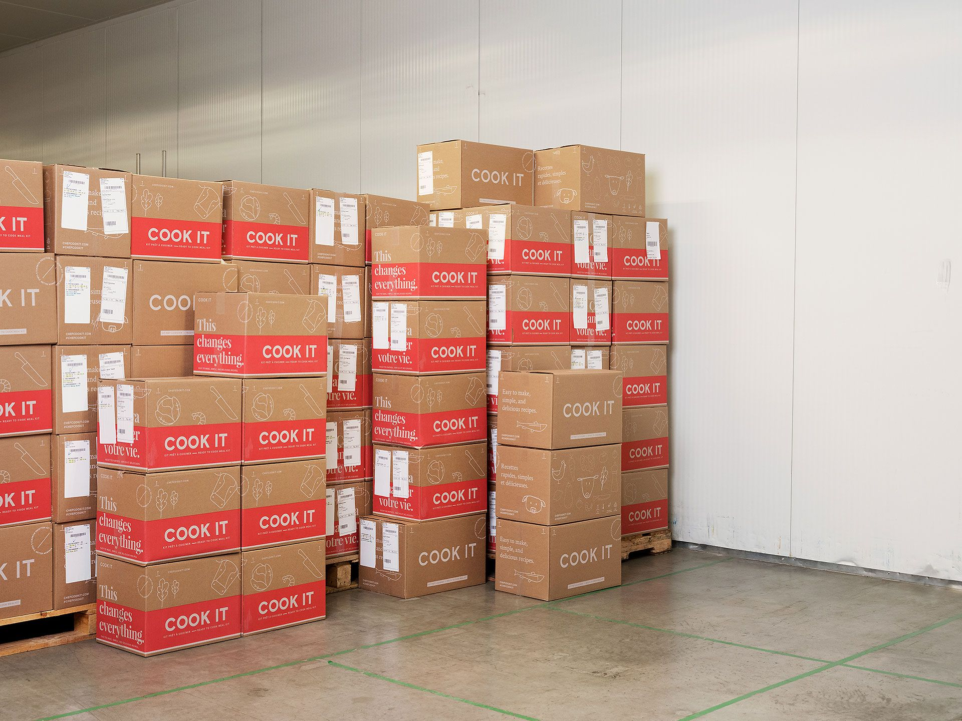 Photo in a bright warehouse of piles of Cook It boxes on palettes and stacked besides.