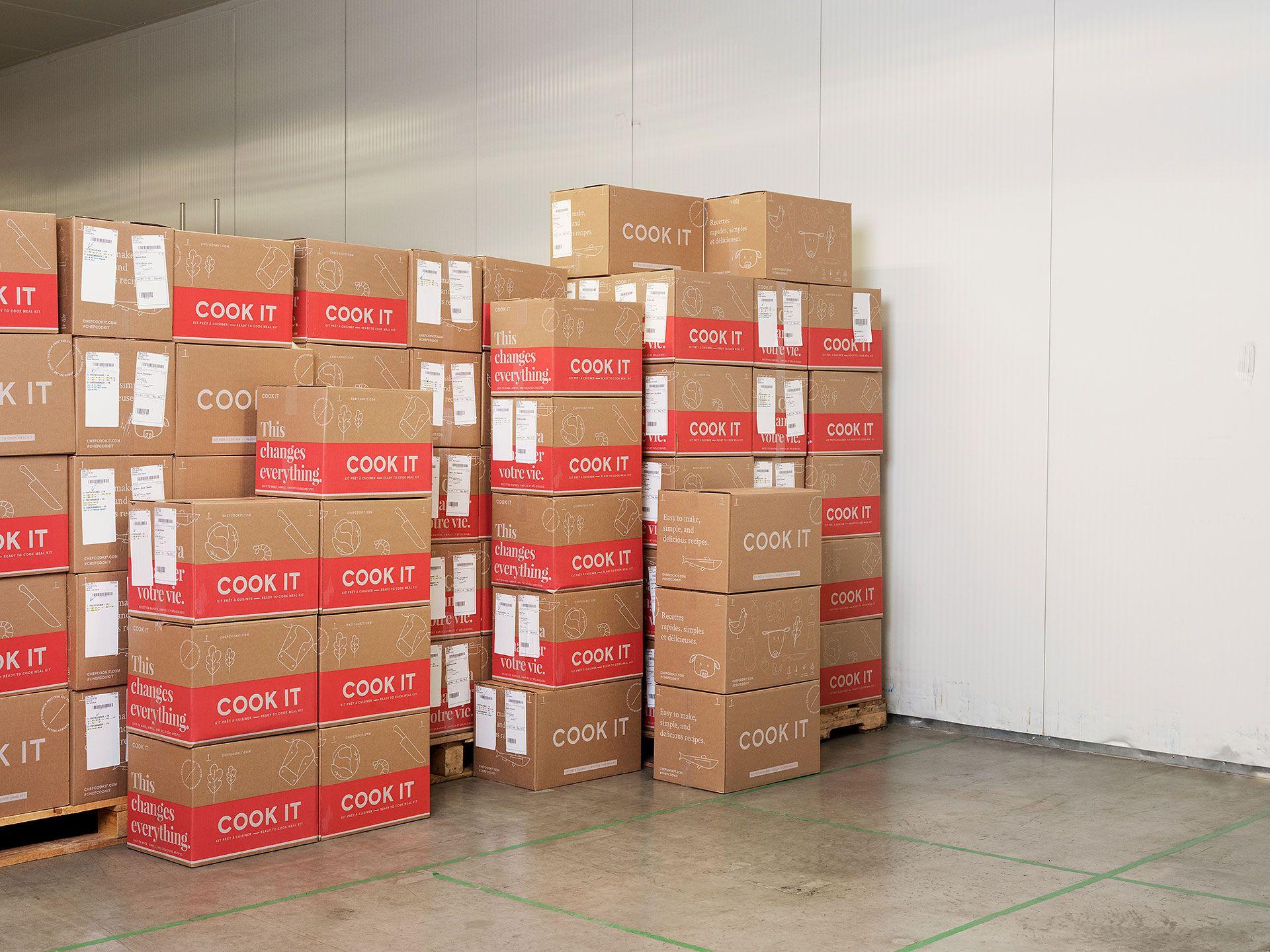 Photo dans un entrepôt lumineux de piles de boîtes Cook It sur des palettes et empilées en plus.