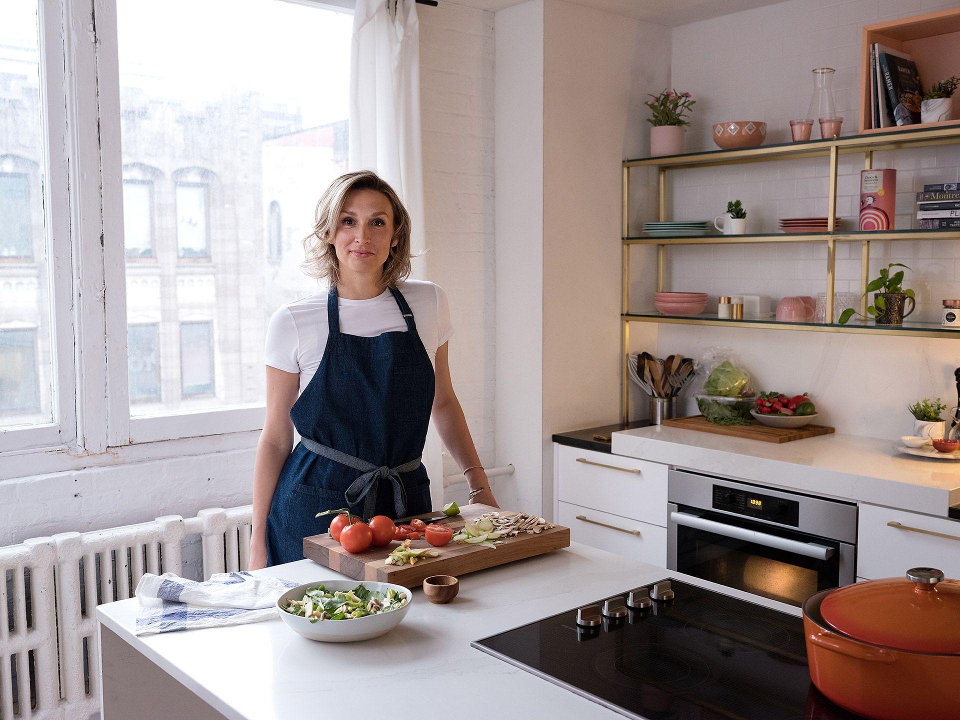 Femme entrepreneur, fondatrice de Cook It, debout dans sa cuisine lumineuse.