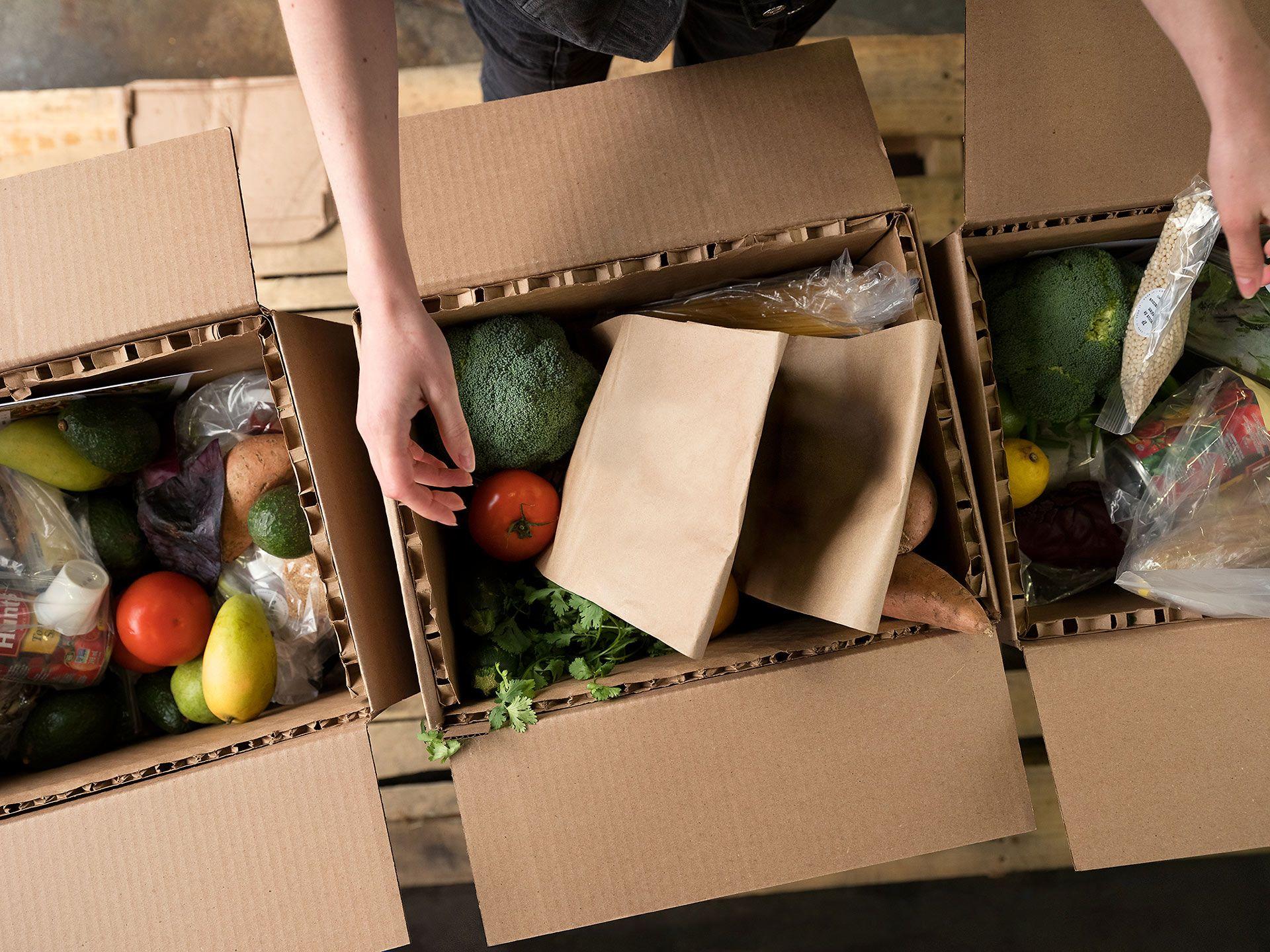 Gros plan de trois boîtes de nourriture en train d'être emballées dans un entrepôt.