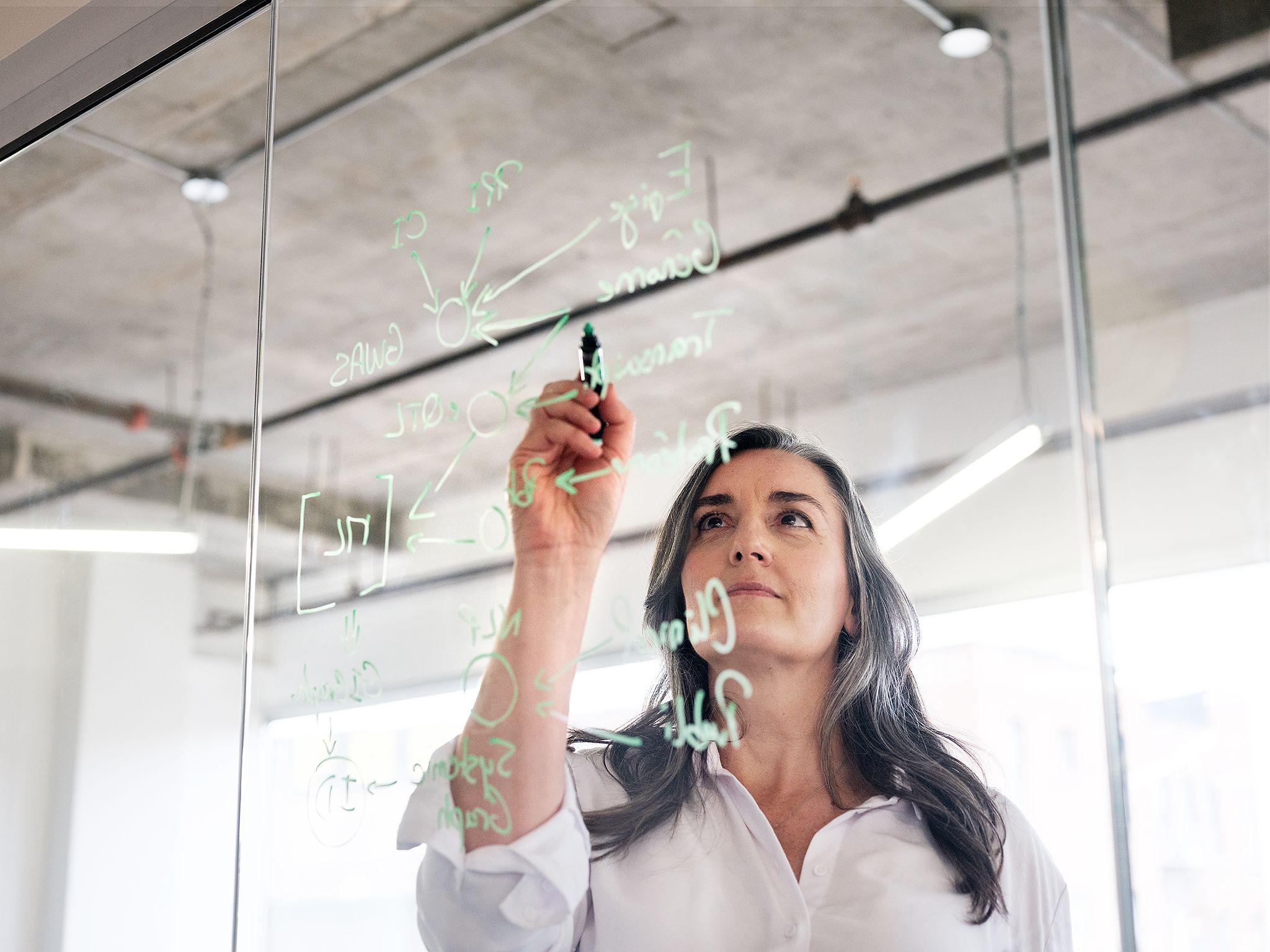 madame écrivant sur une tableau transparent de plastique