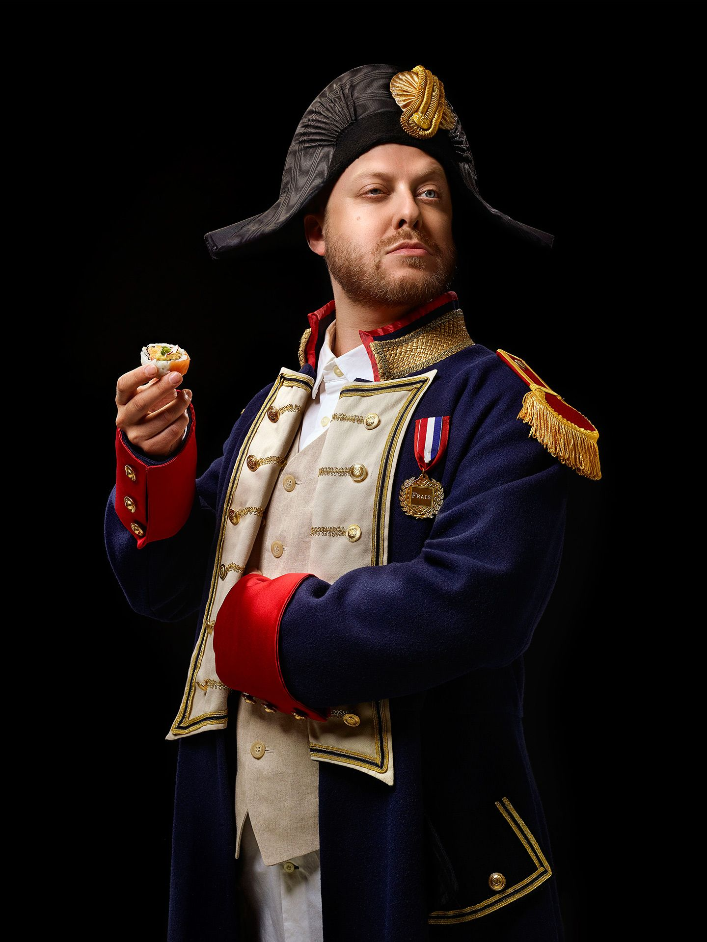 portrait of Guillaume Lambert dressed and posing as Napoleon holding a sushi by Jocelyn Michel for Voir Restos Guide