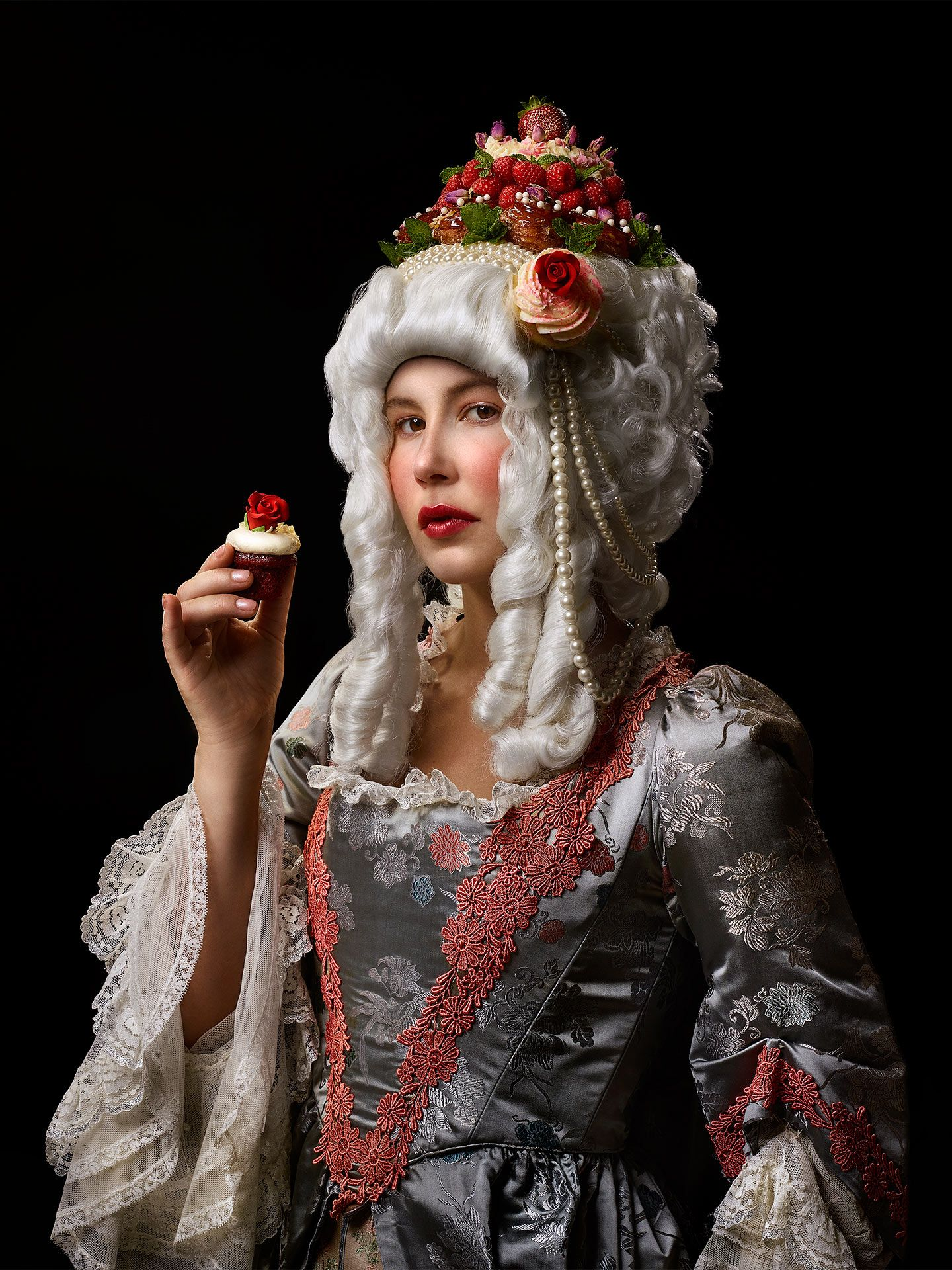 portrait of Juliette Gosselin dressed as Marie Antoinette with cake atop her wig holding a little cupcake by Jocelyn Michel for Voir Guide Restos