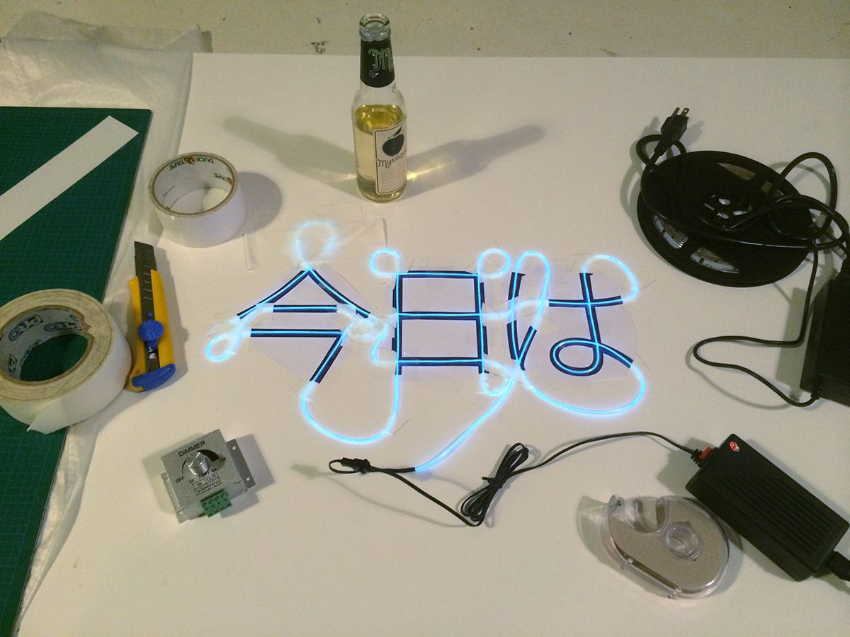 japanese letter being traced with blue light-up neon