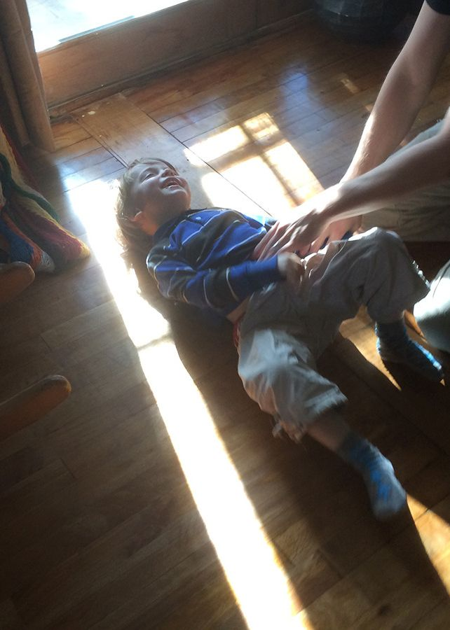 young blond boy laughing being tickled on the floor face in the sun by Guillaume Simoneau