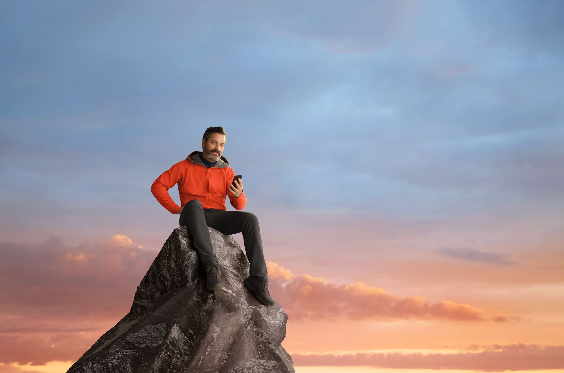 A man is proudly sitting at the top of a mountain, his cellphone in his hand. The sky is a beautiful peach sunset.