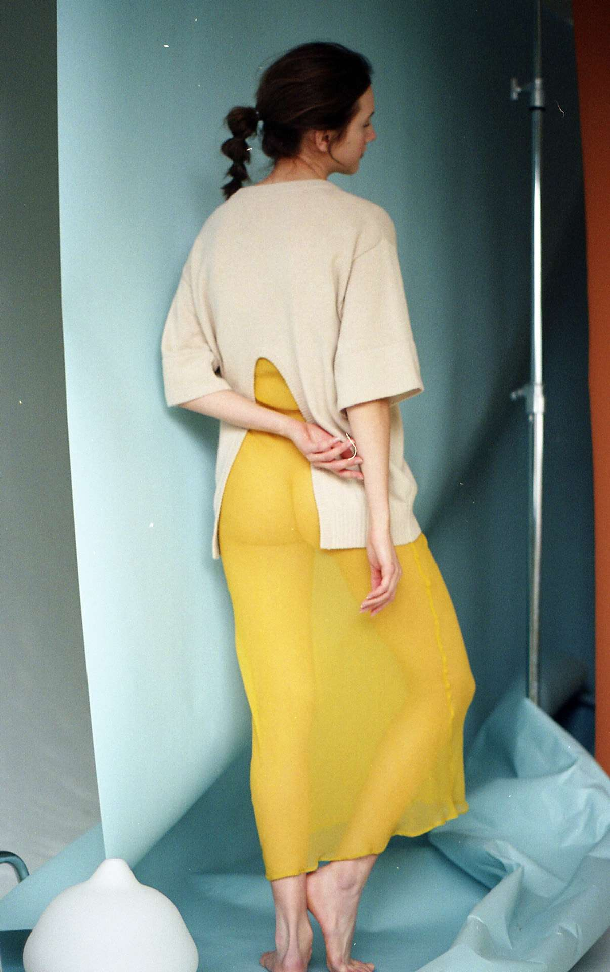 female model wearing see-through yellow dressed exposing her butt and beige cardigan on background made of crumpled paper photographed by Naomie from Studio TB
