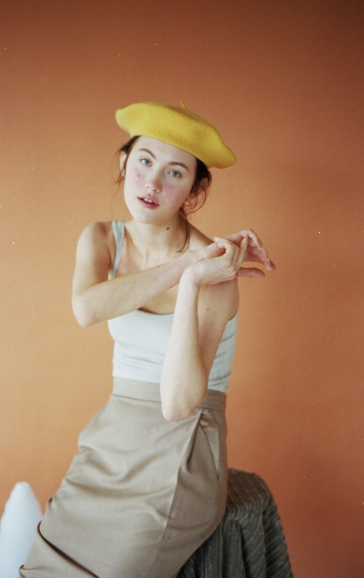 female model Jana sitting on stool wearing beige tight skirt white tank top and yellow beret looking at camera photographed by Naomie from Studio TB for project Sculpting Jana