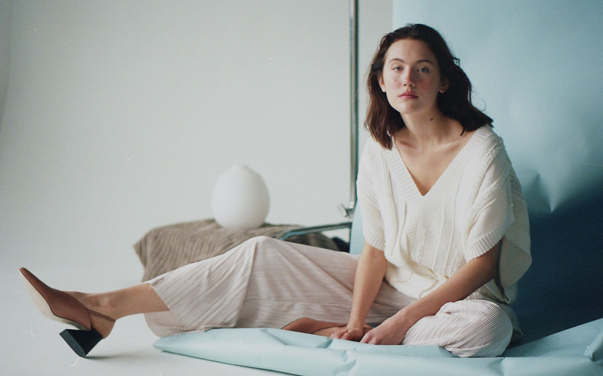 female model Jana sitting on ground on light blue paper background wearing white knit sweater and large white pants with brown pointy shoes looking at camera photographed by Naomie from Studio TB for project Sculpting Jana