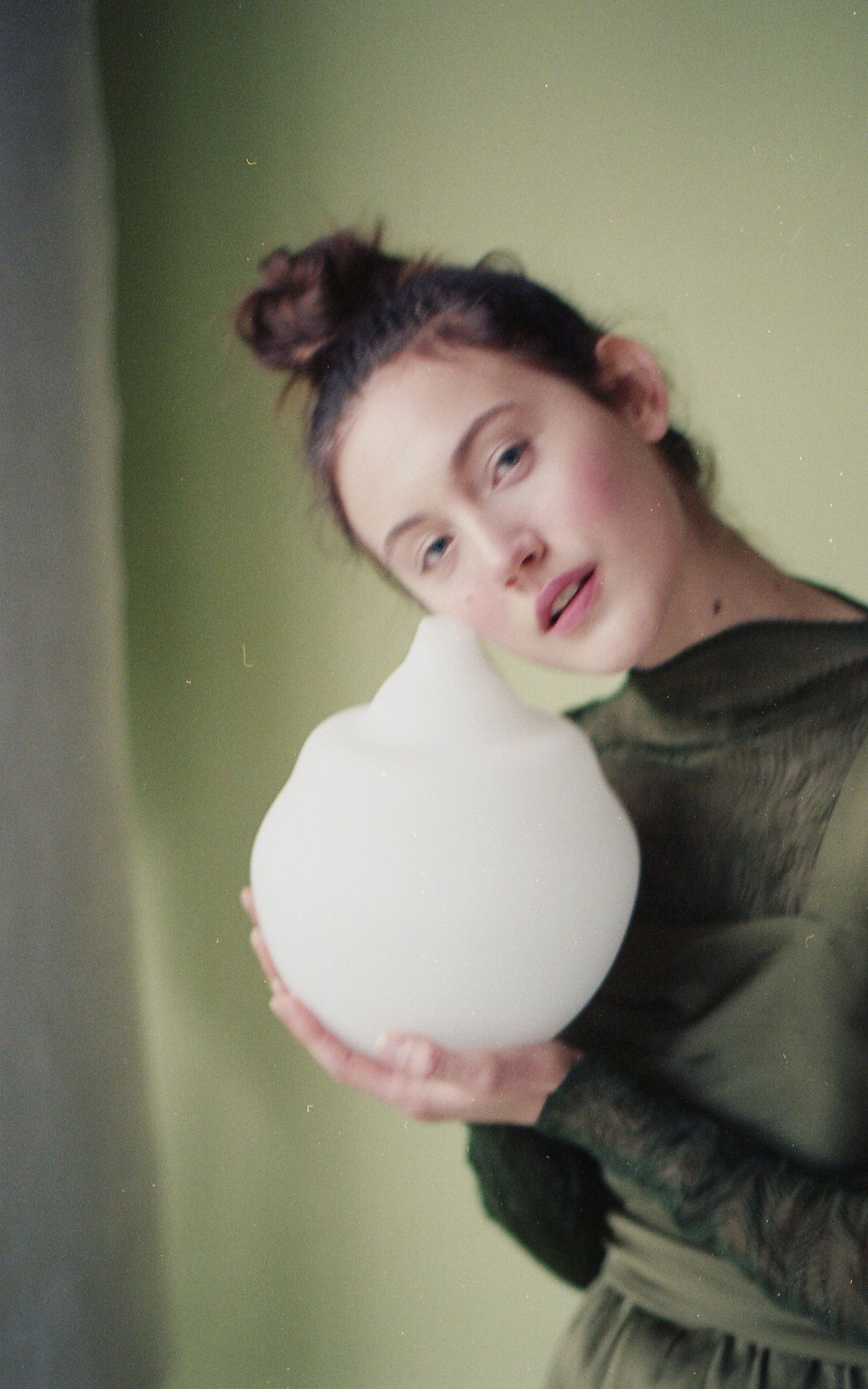 female model Jana on light green paper background holding small white vase in her hands wearing dark green clothes looking at camera photographed by Naomie from Studio TB for project Sculpting Jana