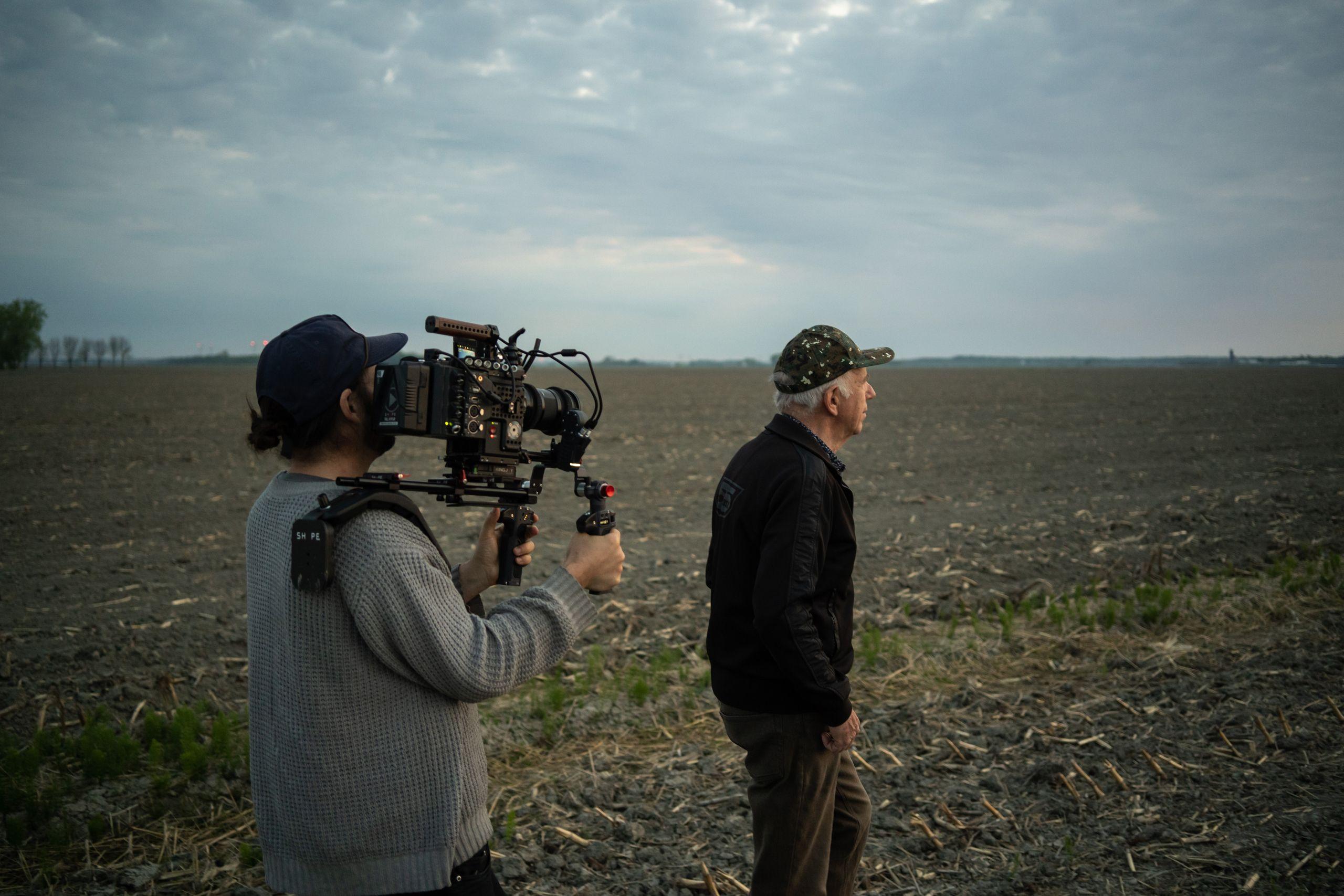 Image des coulisses. On voit un caméraman qui filme Jonas Sivo en train de marcher dans son champ.