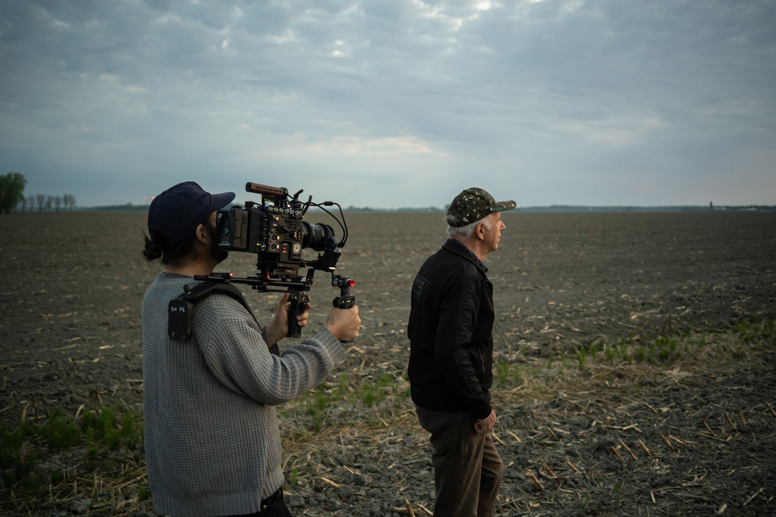 Behind the scenes picture. We see a camera man filming Jonas Sivo walking in his field.