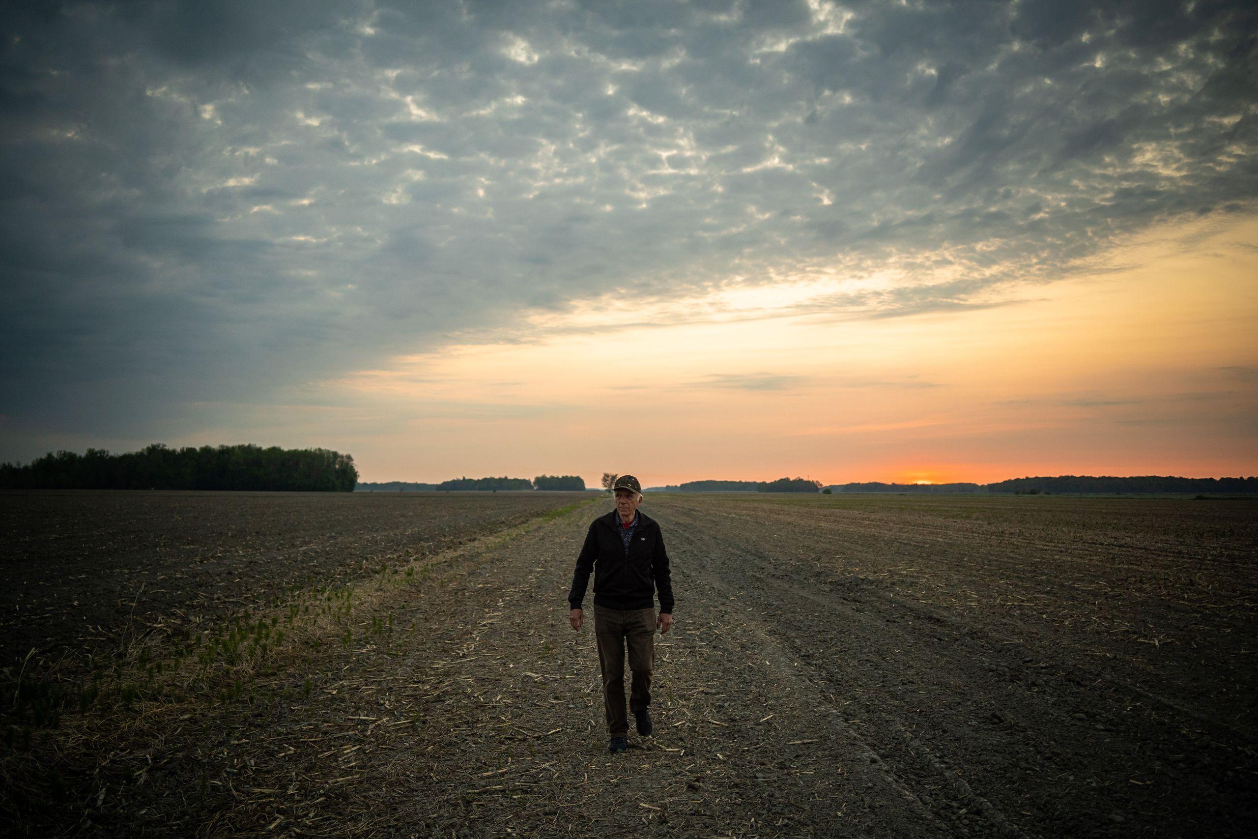 Photo de Jonas Sivo marchant dans son champ de production avec un coucher de soleil orange et des nuages texturés dans le ciel.