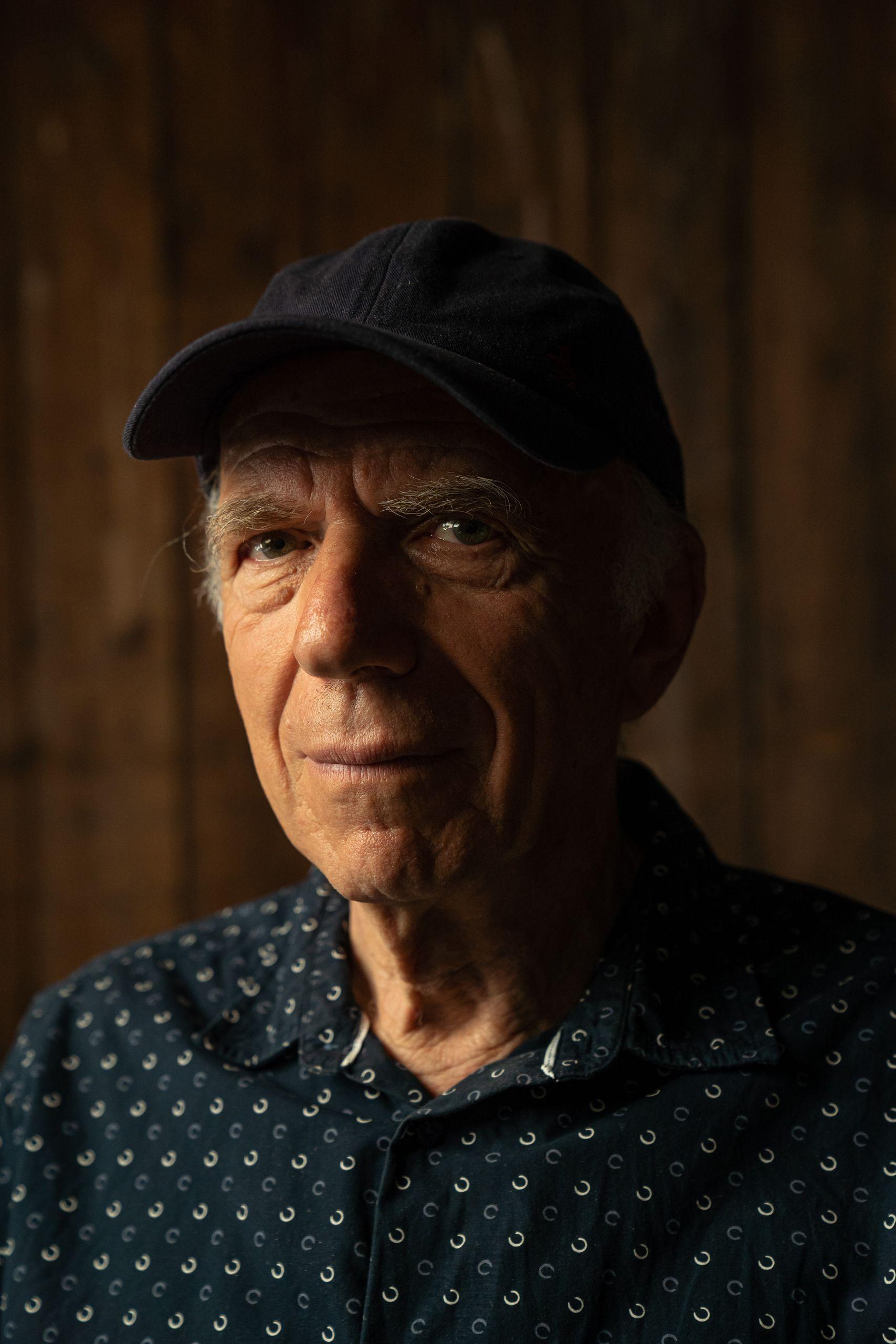 Portrait d'un homme un peu âgé. Il a un beau sourire, des yeux pétillants, porte une chemise bleu foncé et une casquette, il est devant le mur d'une écurie. Janos Sivo, fondateur de Maison Sivo.