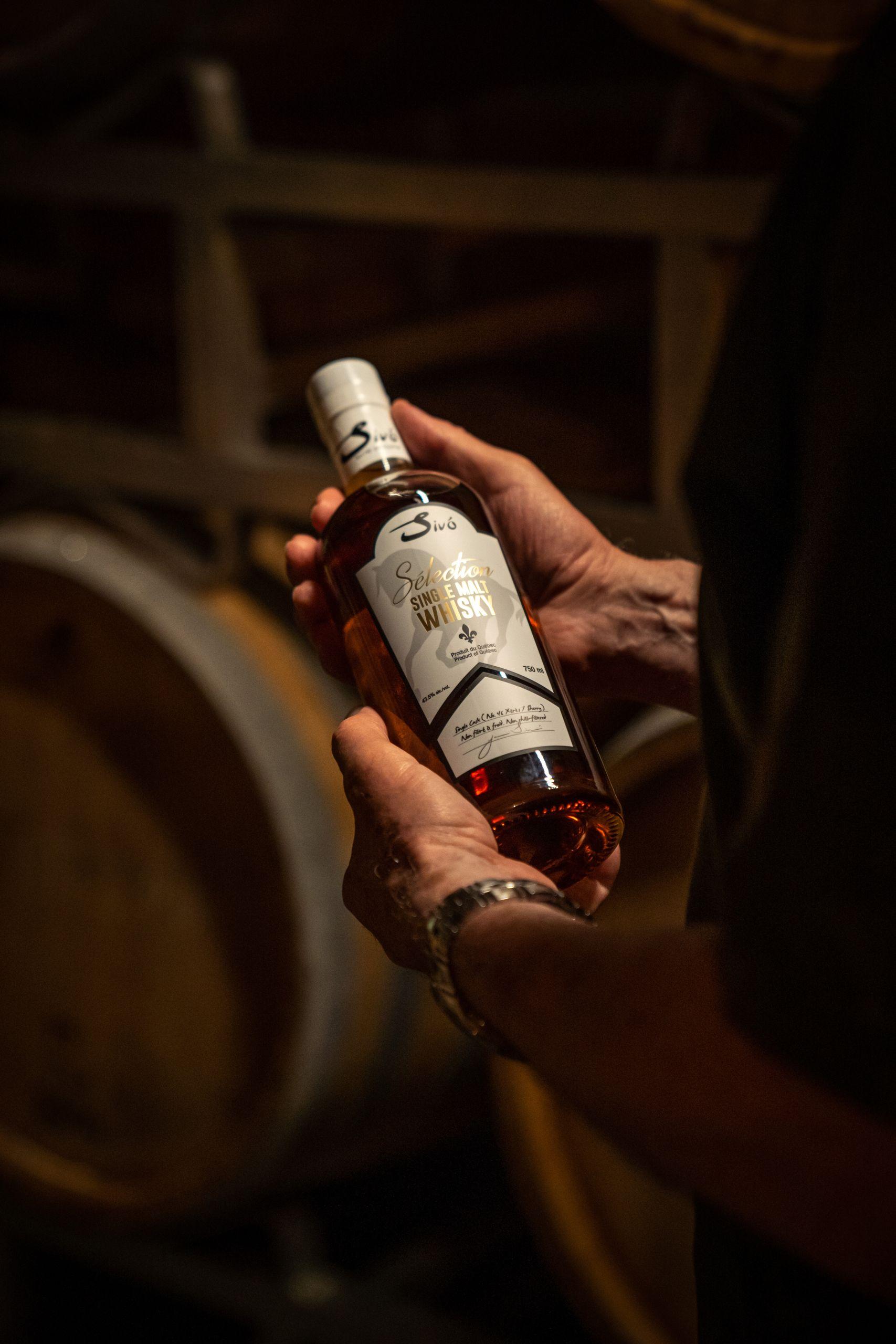 Dans la grange de distillation, Janos Sivo, fondateur de la Maison Sivo, tient une bouteille de whisky single malt fabriqué au Québec. La photo est un gros plan sur les mains qui tiennent la bouteille.