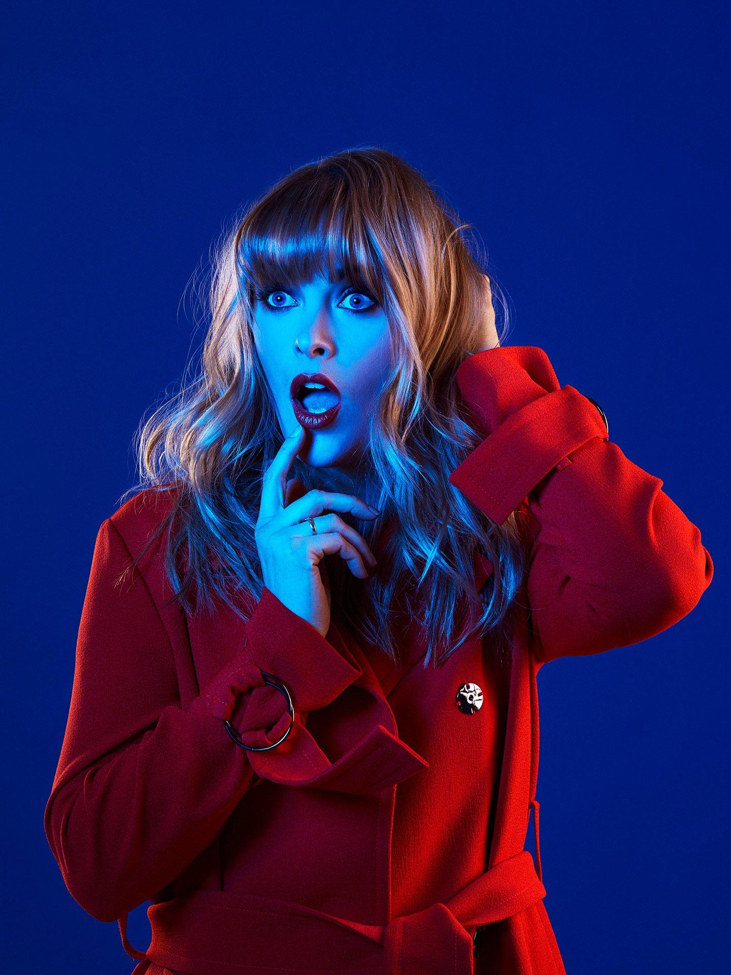 Portrait scénique d'Andréanne A Malette à l'air surpris en trench-coat dans une lumière bleue et un fond bleu par Jocelyn pour le Journal de Montréal