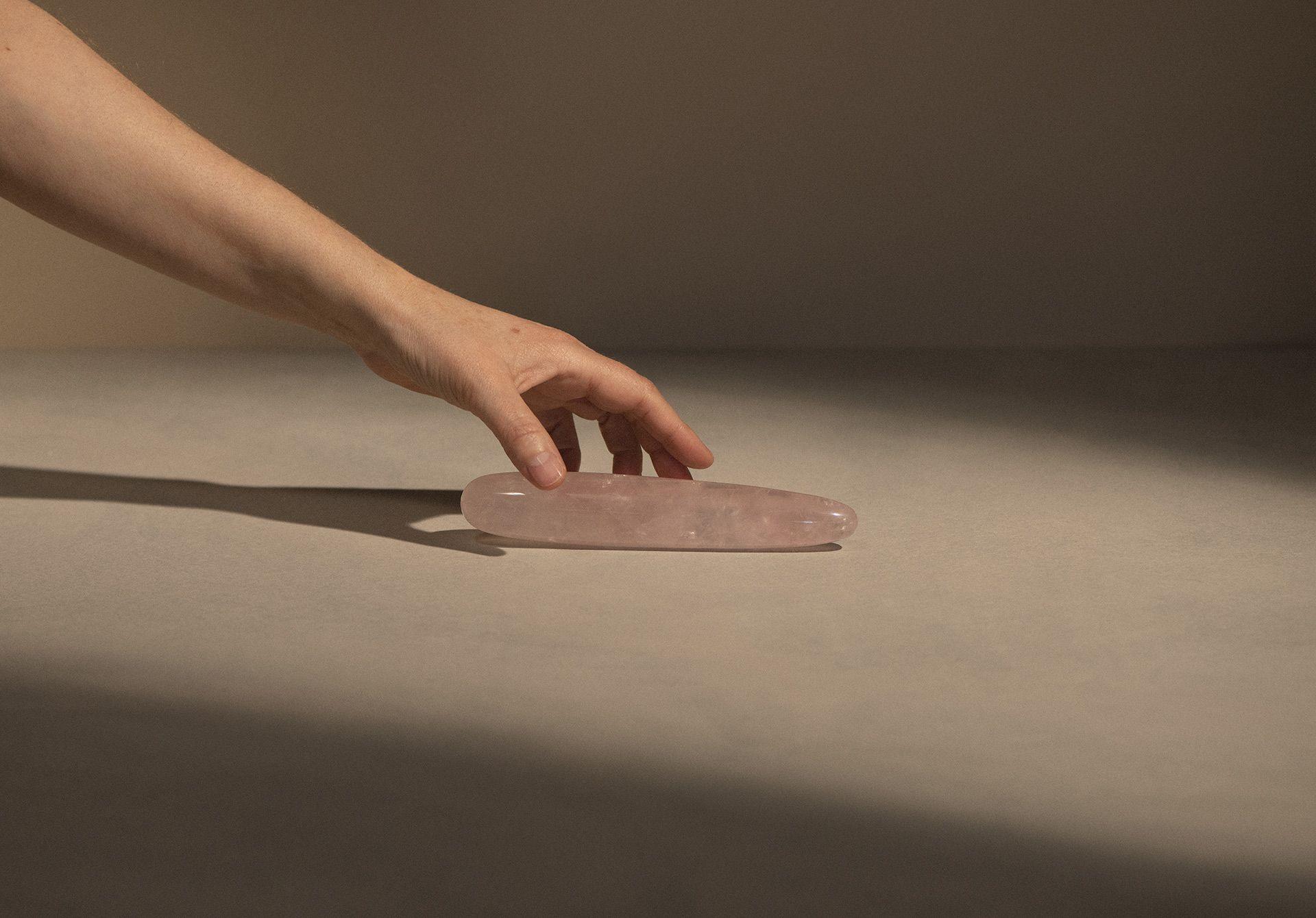 Dildo, Gode à baguette en quartz rose sur un fond beige avec une main qui le saisit.
