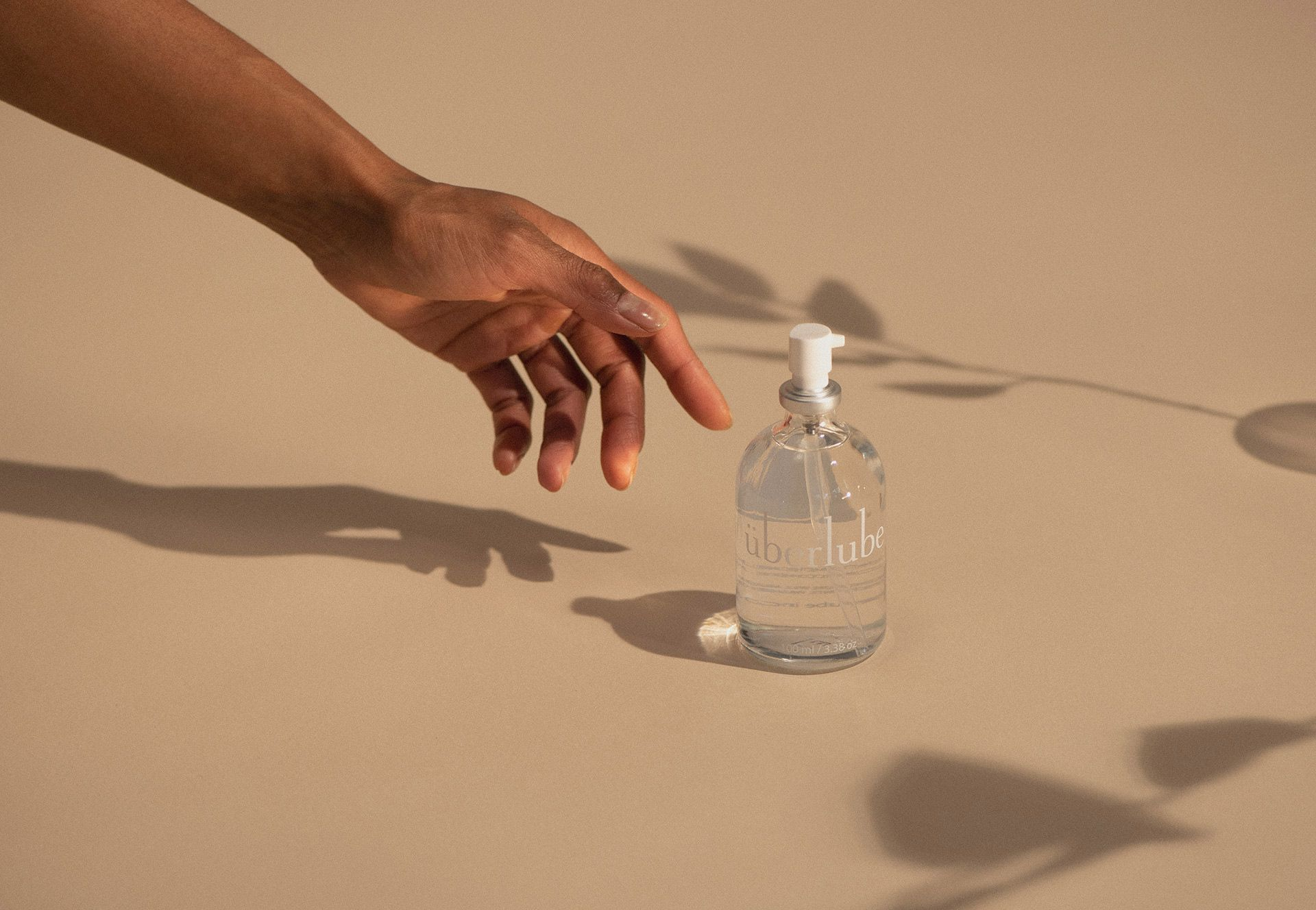 Hand reaching for a clear pump bottle of Uberlube sex lubricant.
