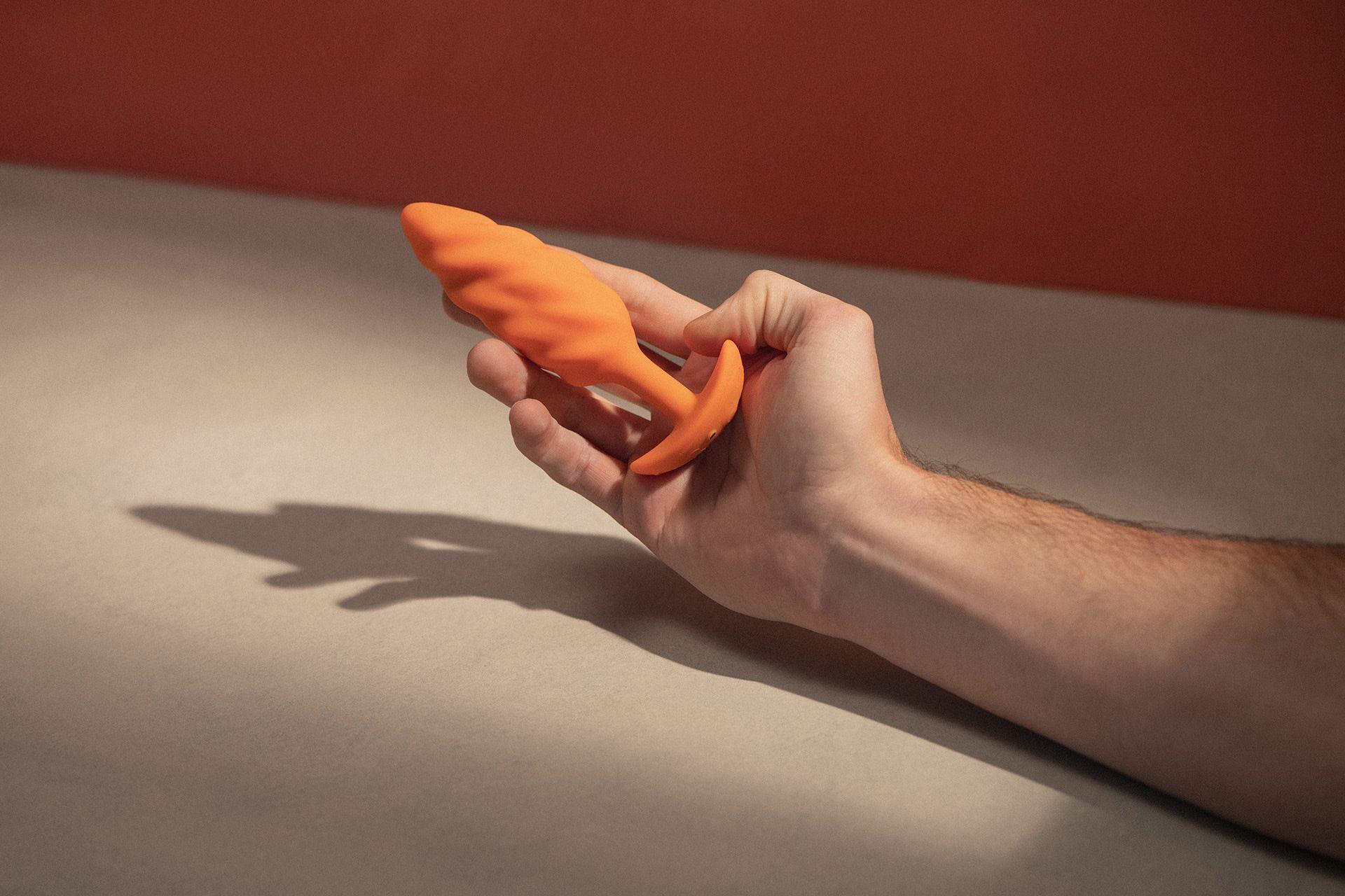 Butt plug orange torsadé vibrant tenu par une main.