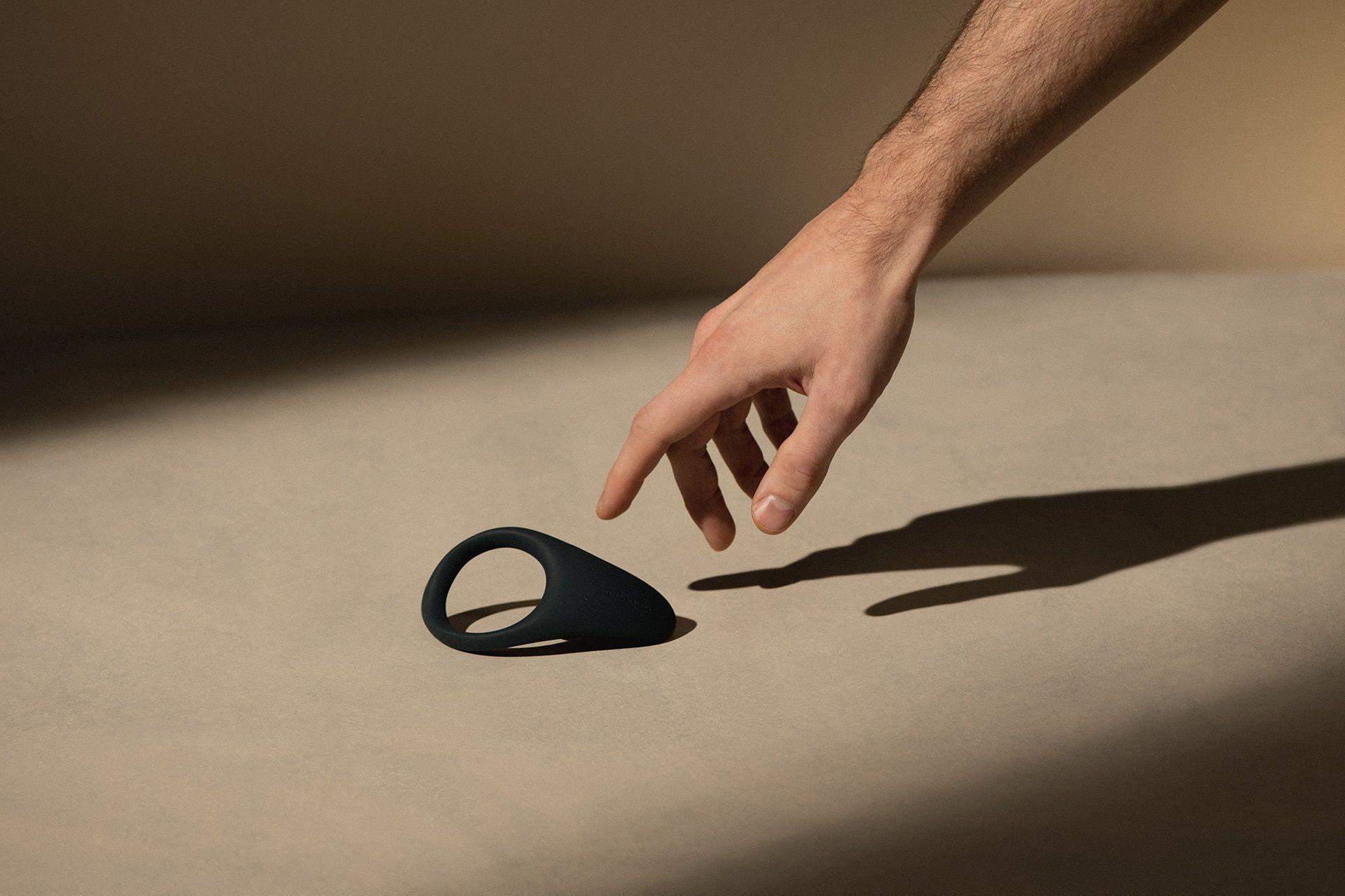 Décor beige en clair-obscur avec une main tendue vers un anneau pénien vibrant noir mat.