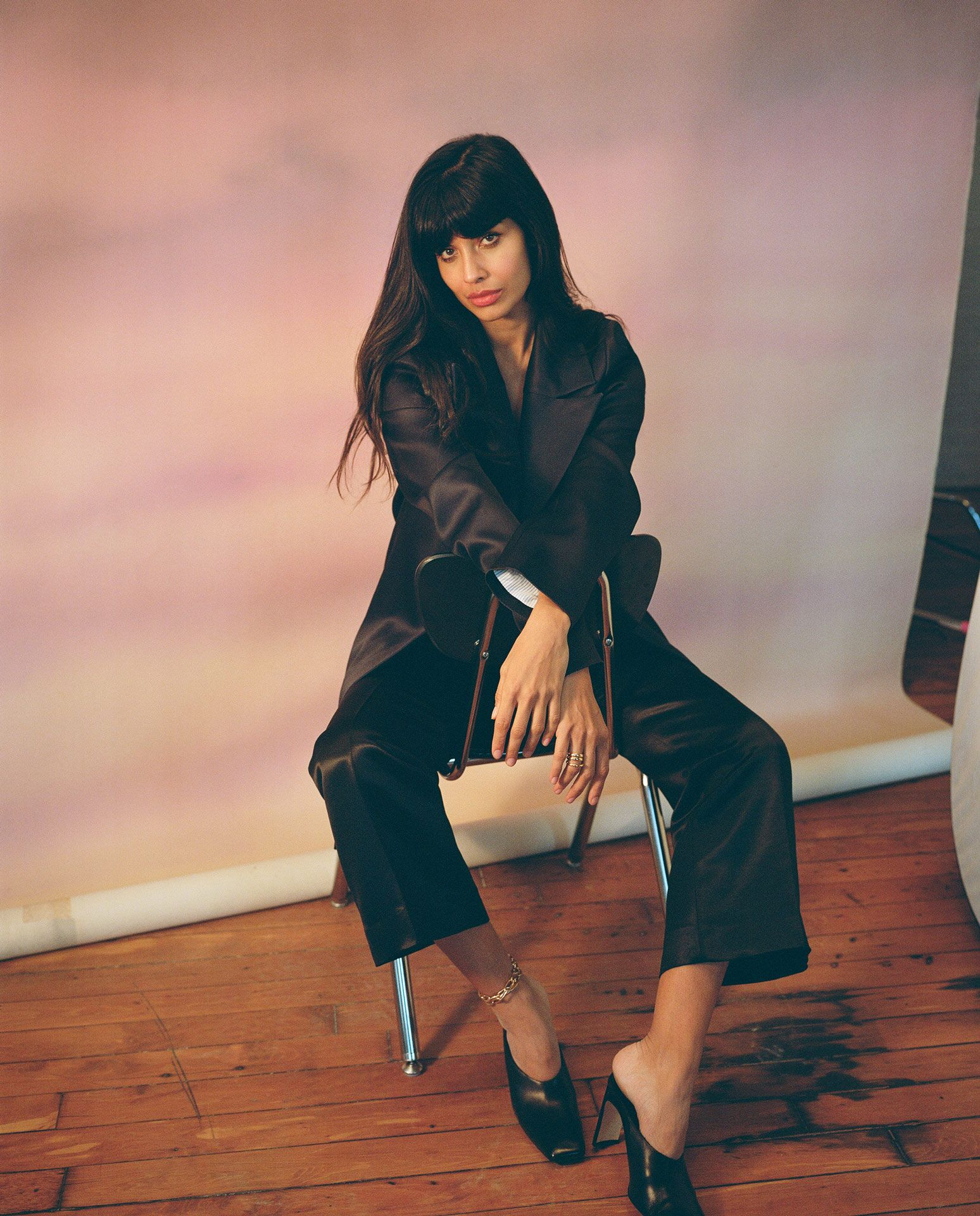 picture of actress Jameela Jamil sitting backward on a chair looking at camera by Oumayma B. Tanfous for Vogue Spain