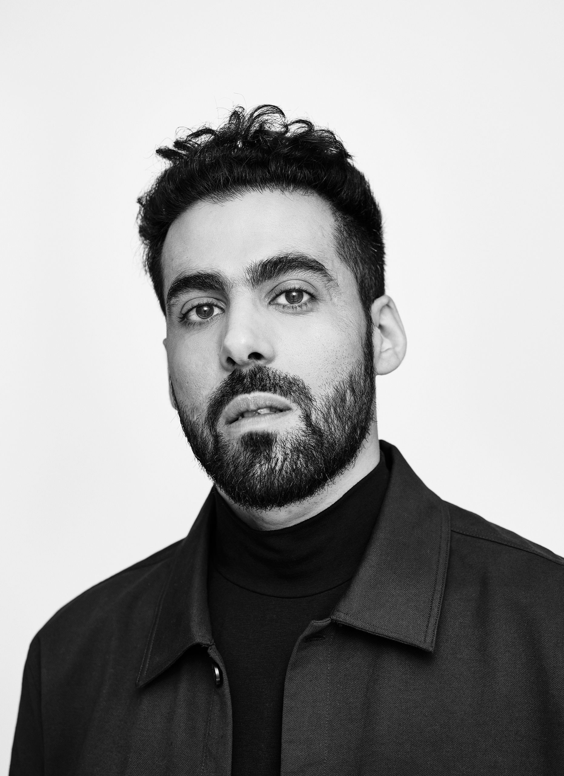 Portrait en noir et blanc de l'humoriste Adib Alkhalidey portant un col roulé et une chemise.