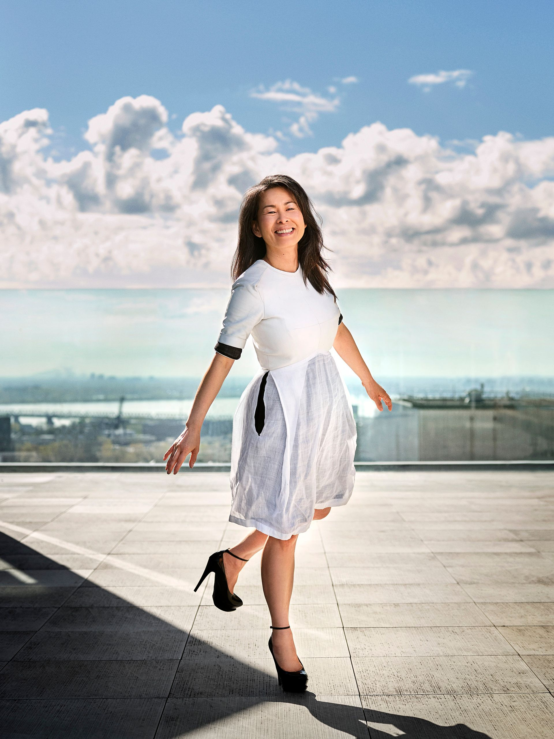 Full body picture of author Kim Thuy walking with energy, almost jumping. She is smiling and wears a white dress, stiletto black shoes.