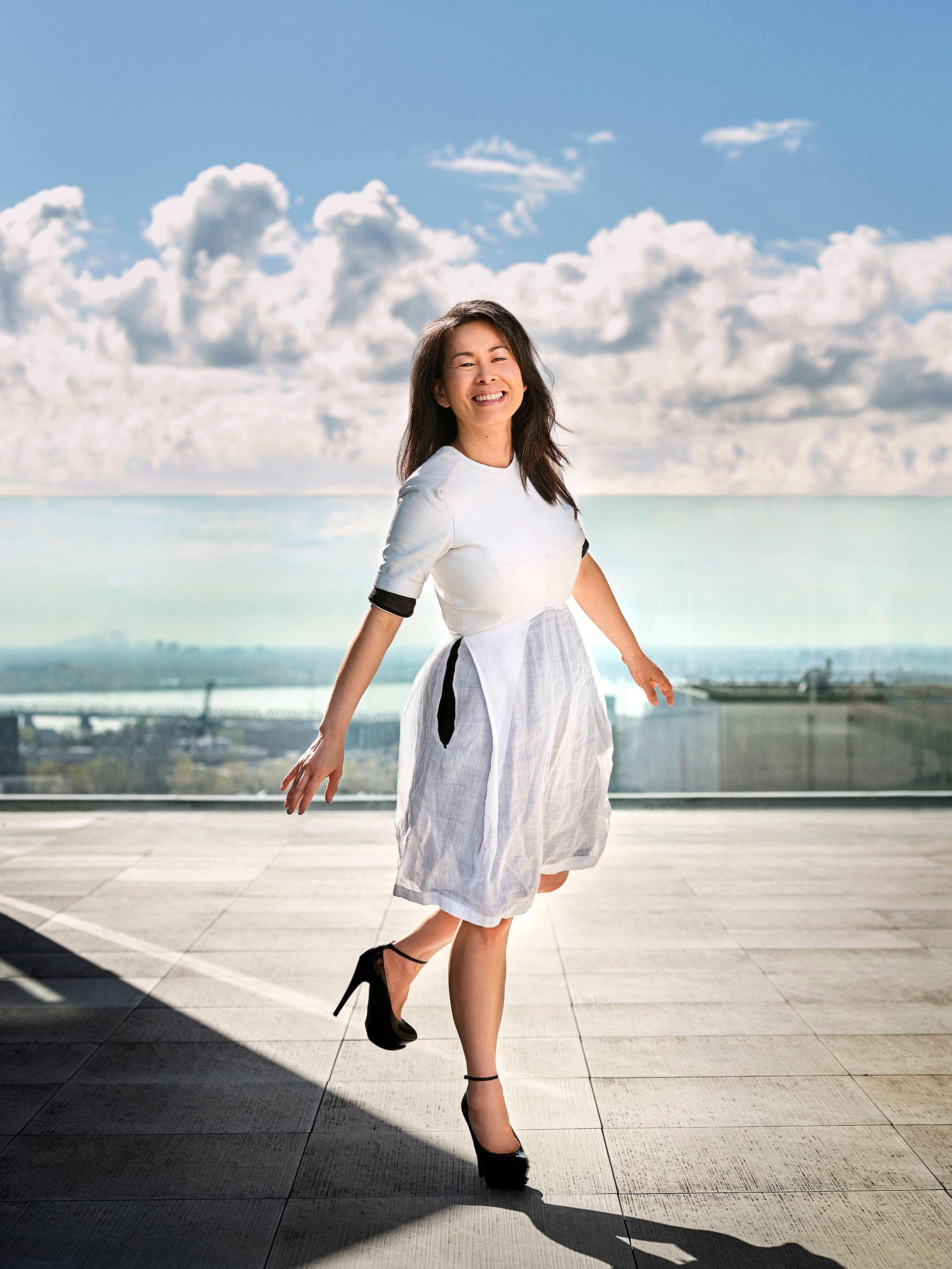 Photo du corps entier de l'auteur Kim Thuy marchant avec énergie, sautant presque. Elle est souriante et porte une robe blanche, des chaussures noires à talon aiguille.